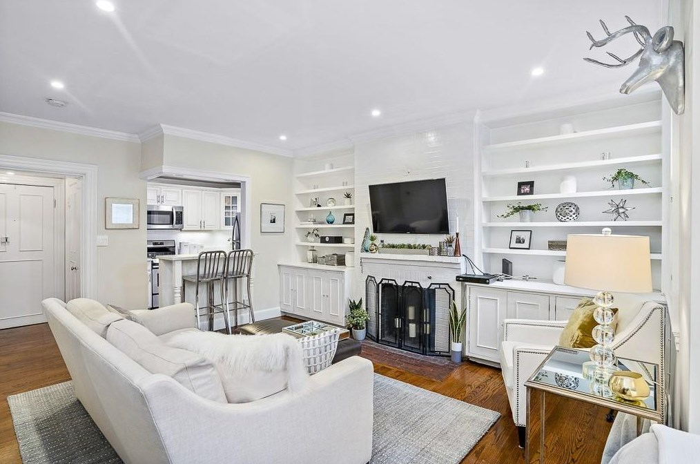 A small living room with a couch facing a fireplace with a TV mounted above it and there's a counter with stools in front of it.