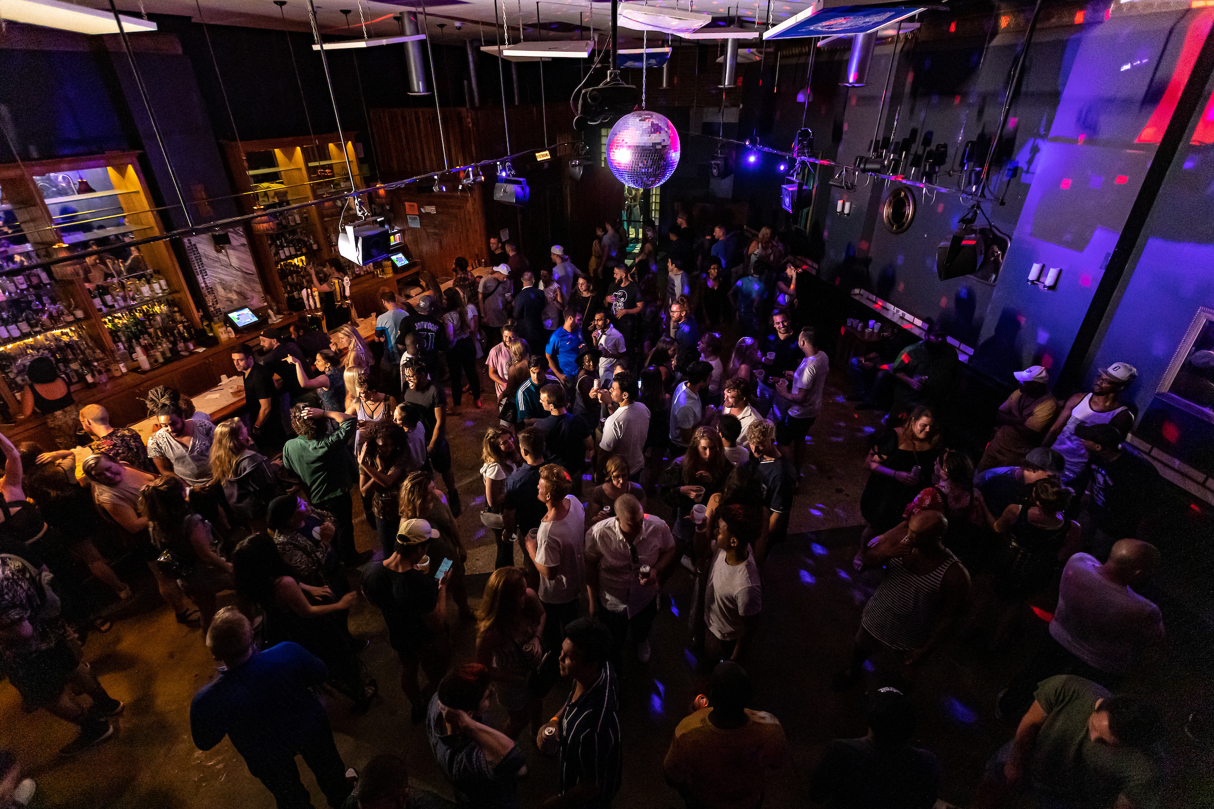 A large group of people gather in a club on the dancefloor beneath a disco ball.