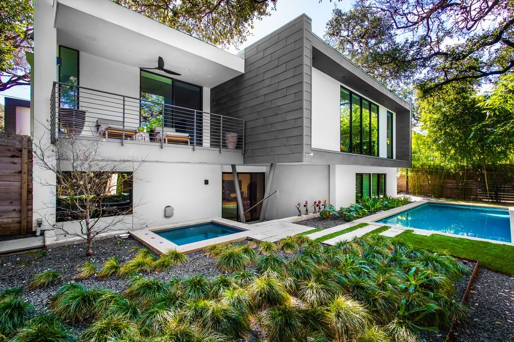 A photo of the back of a two-story modern house with a balcony and porch on the left and a cantilevered upstairs room that sticks out over the pool and has gray shingle siding. The rest of the house is stucco
