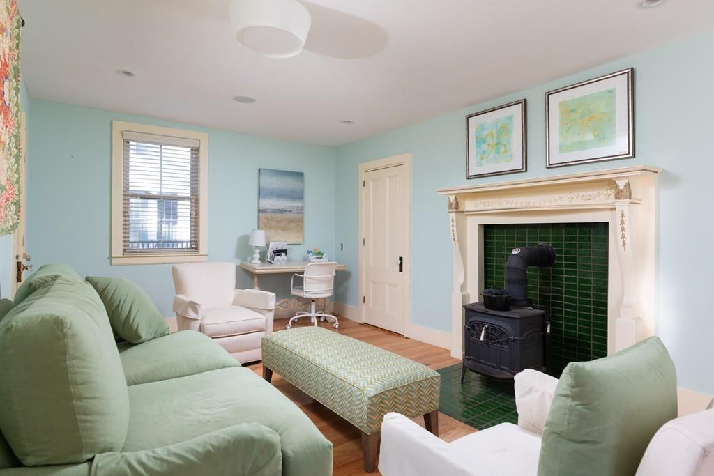 A small, square room with plush furniture arranged around an antique stove.