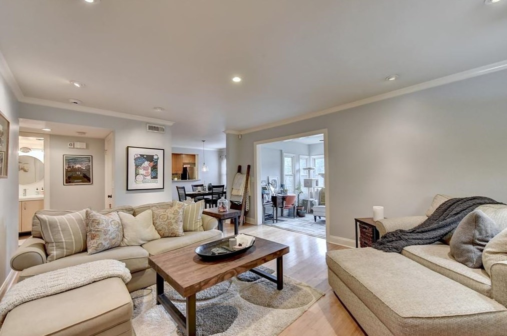 A white room with much beige furniture and a coffee table.