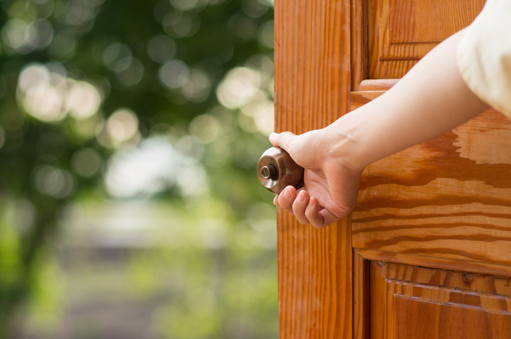 A woman's hand opening the front door of a house.