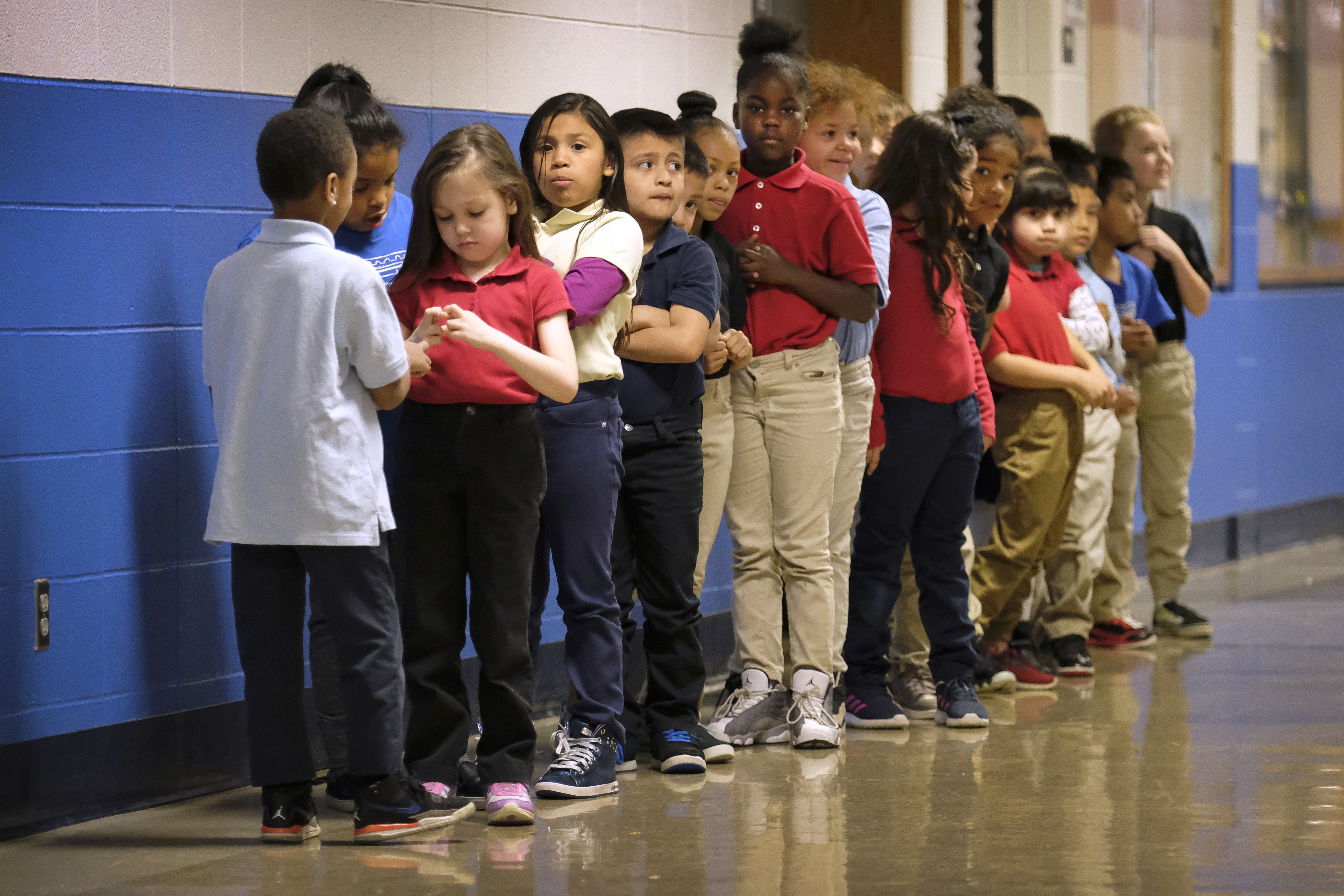 Elementary students in a line in a hallway at Thomas Gregg Neighborhood School, an elementary school in Indianapolis, Indiana. —April, 2019