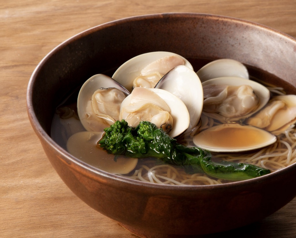 A brown bowl with soba noodles, a translucent broth, clams, and a green vegetable.