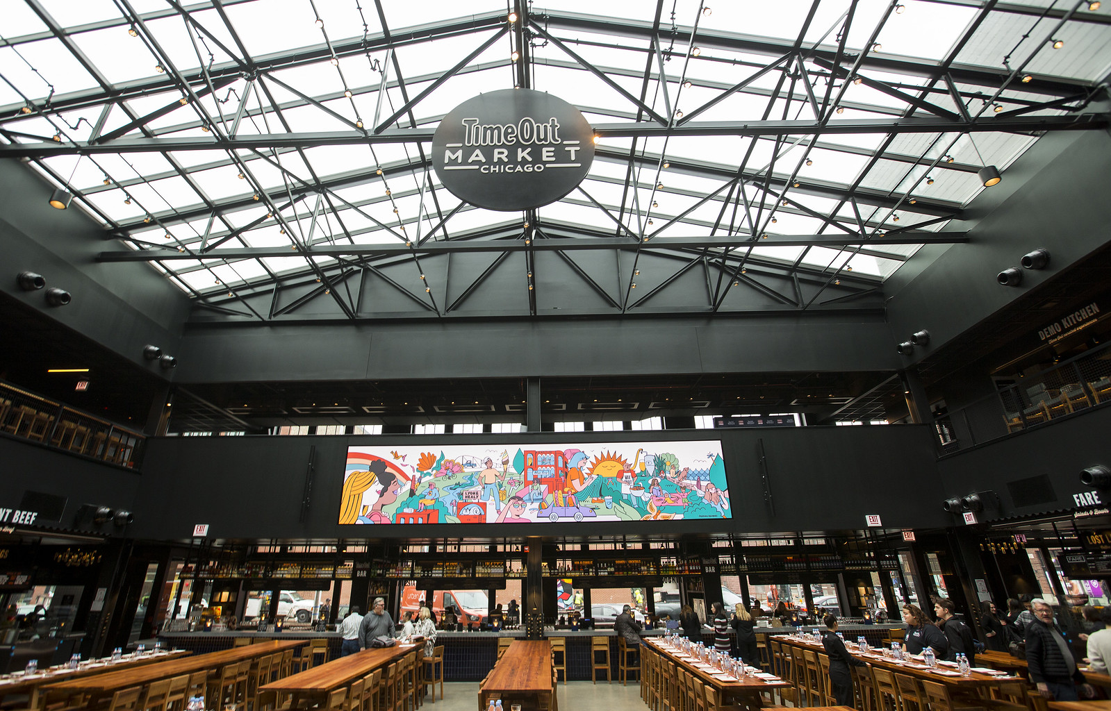 A skylight and a giant video screen hang over a large dining room with communal seating.