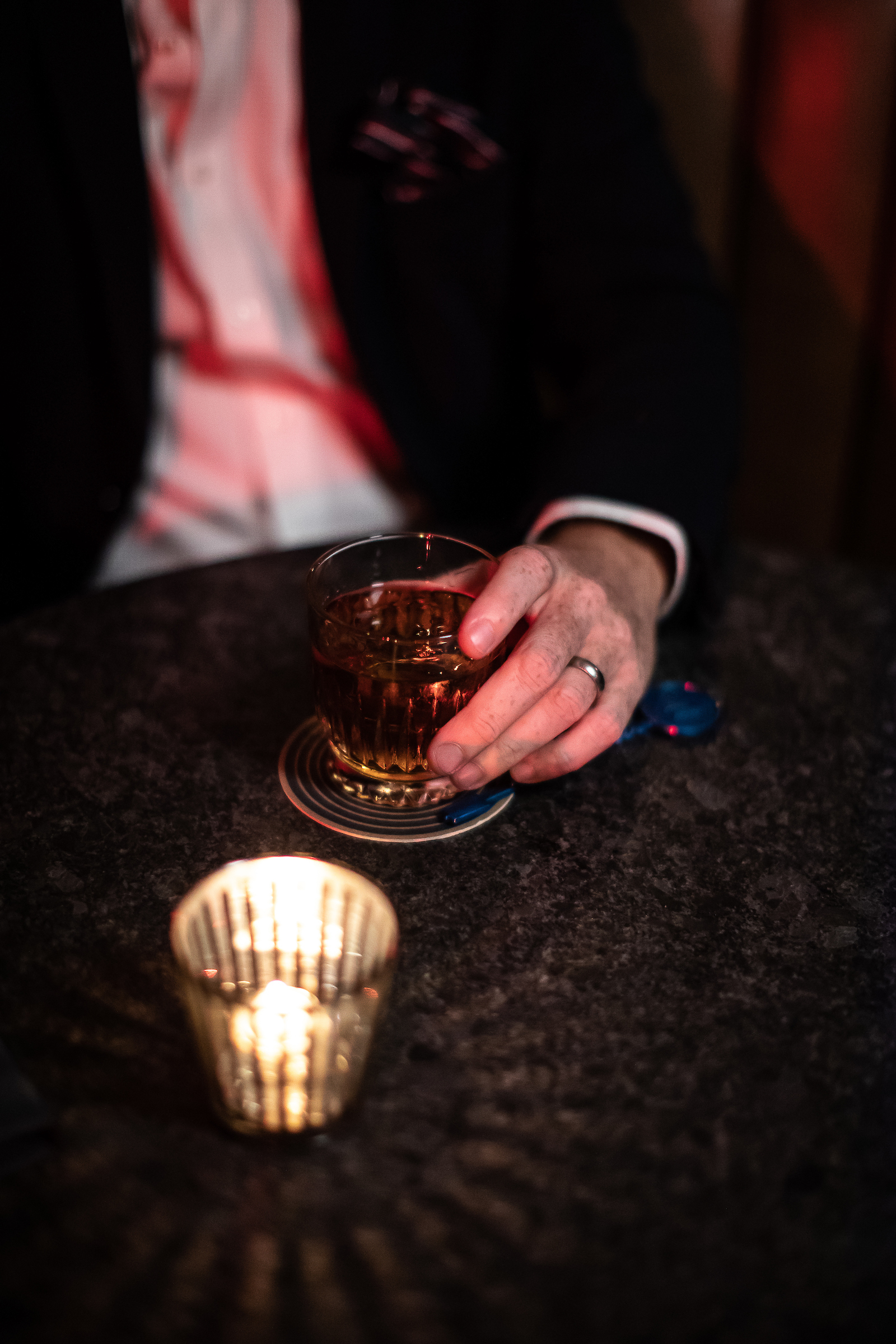 A man with a ring on his hand cradles a tumbler of whiskey next to a tea light at Willis Show Bar.