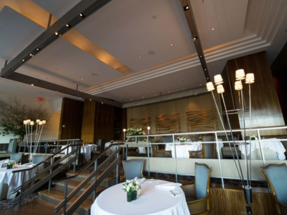 Tables with with tablecloths decorate the two-tiered dining room at Per Se