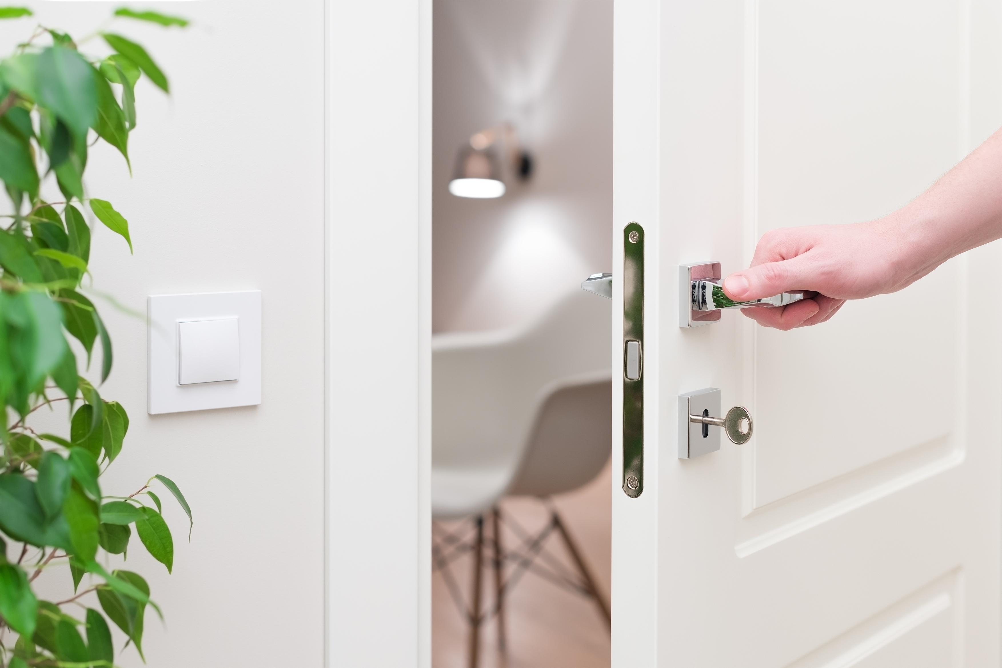 A hand opening a door.
