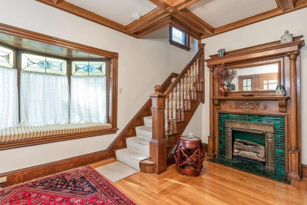 An entry foyer with a decorative fireplace with a mantel and a staircase.
