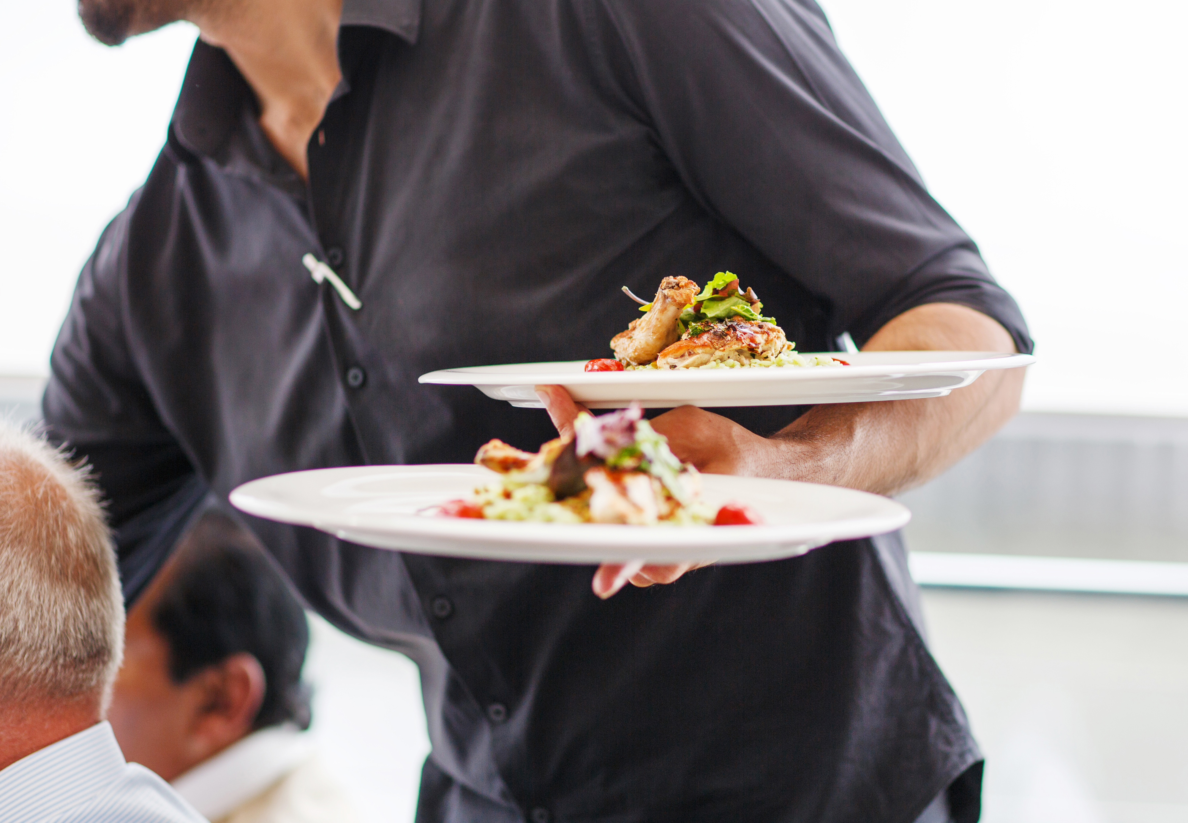 A waiter serving dishes to a table of diners