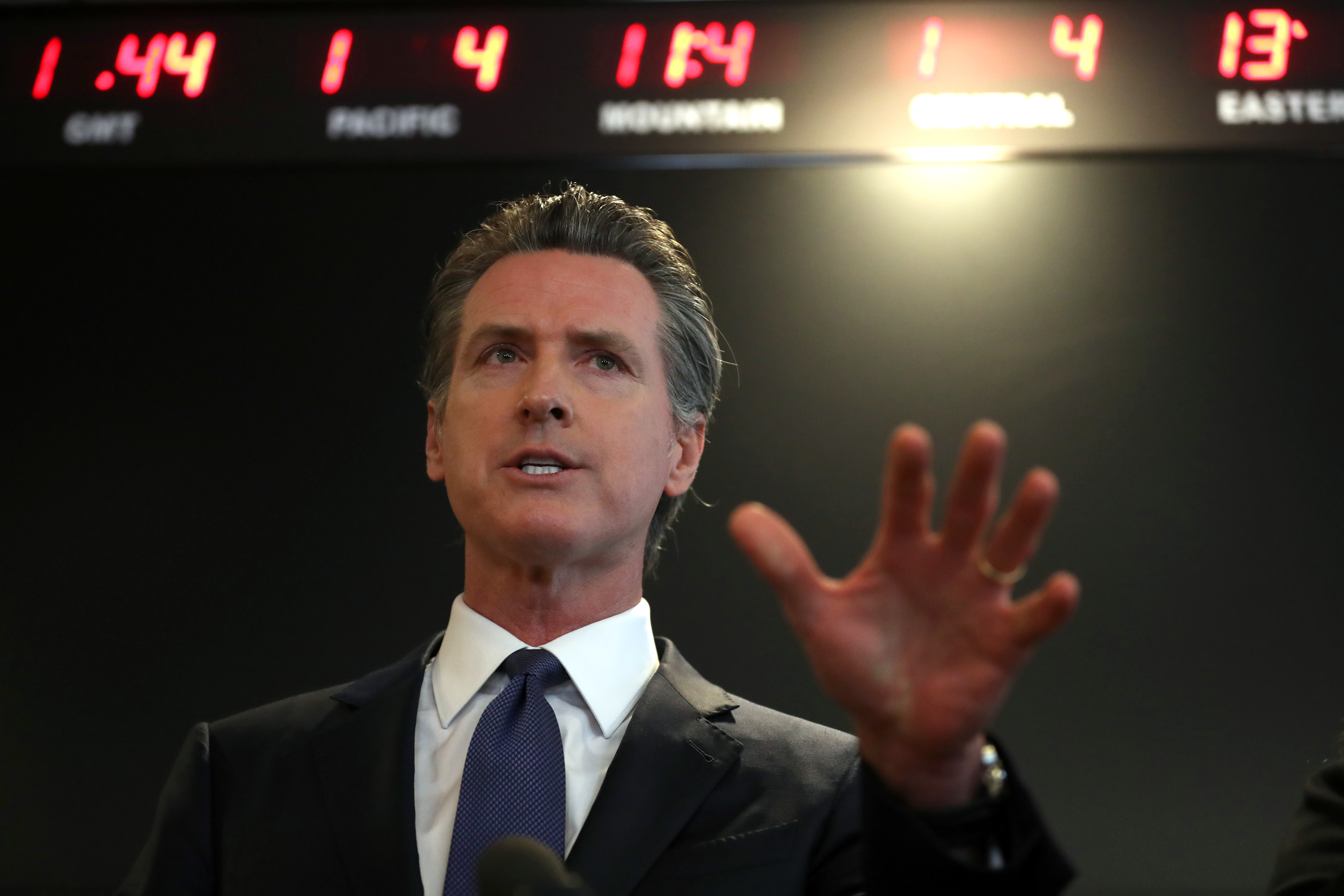 A low-angle photo of a man in a suit speaking with one hand upraised in an emphatic gesture.