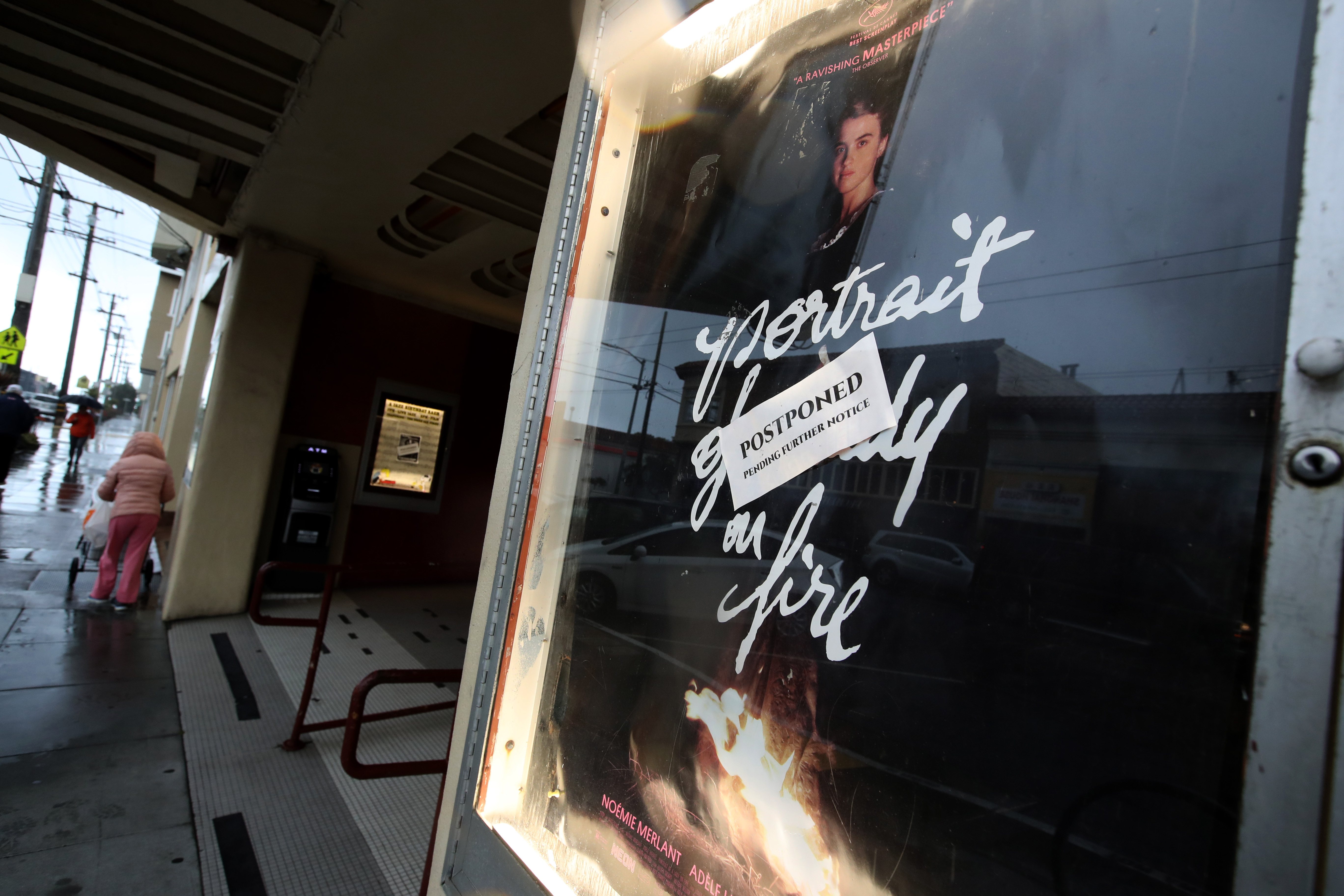 A postponed sign is displayed on a movie poster at Balboa Theater.