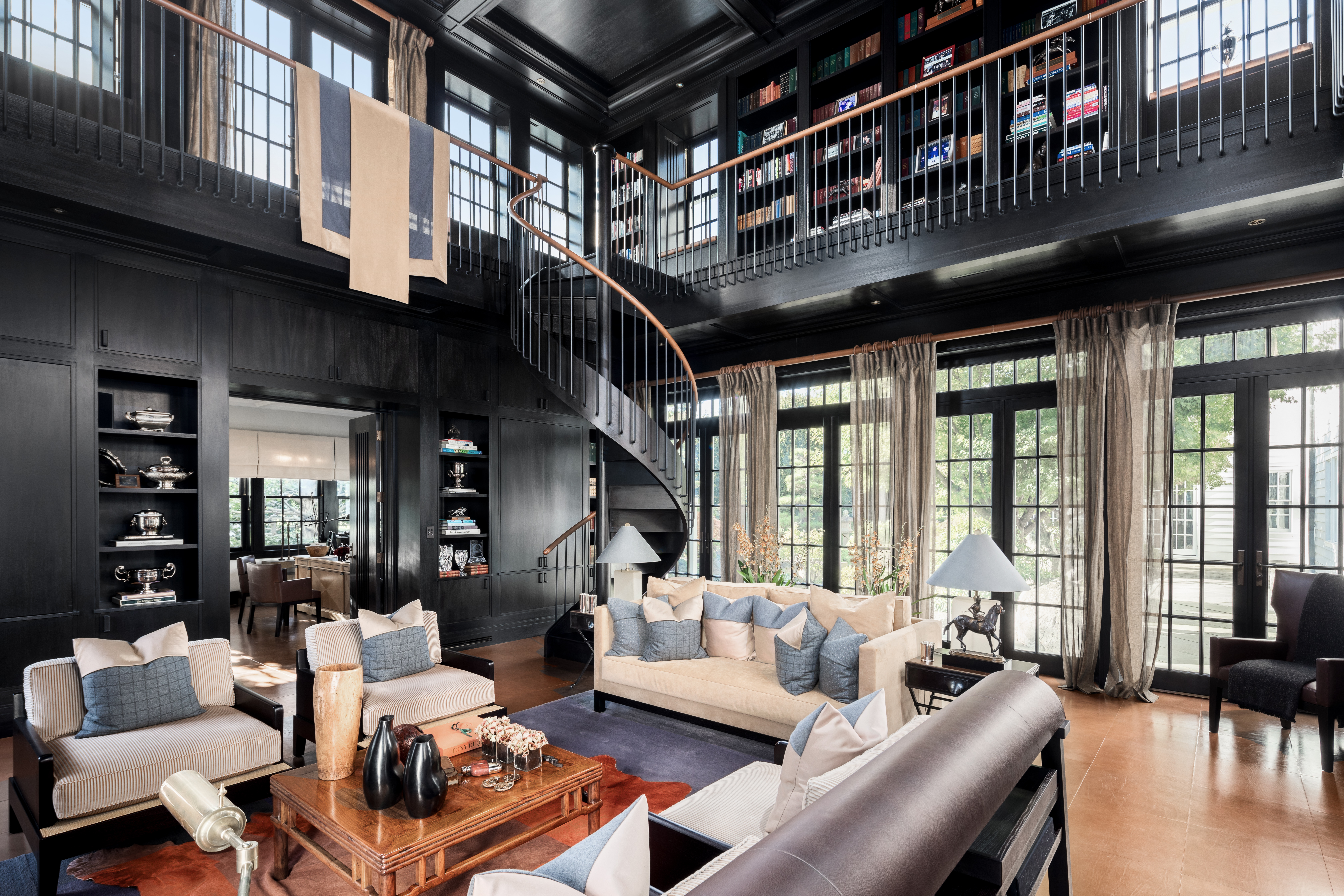 A two-story library has black walls and cream colored furniture. A balustrade wraps around the second level. On the first level, french doors let out onto the landscaped grounds.
