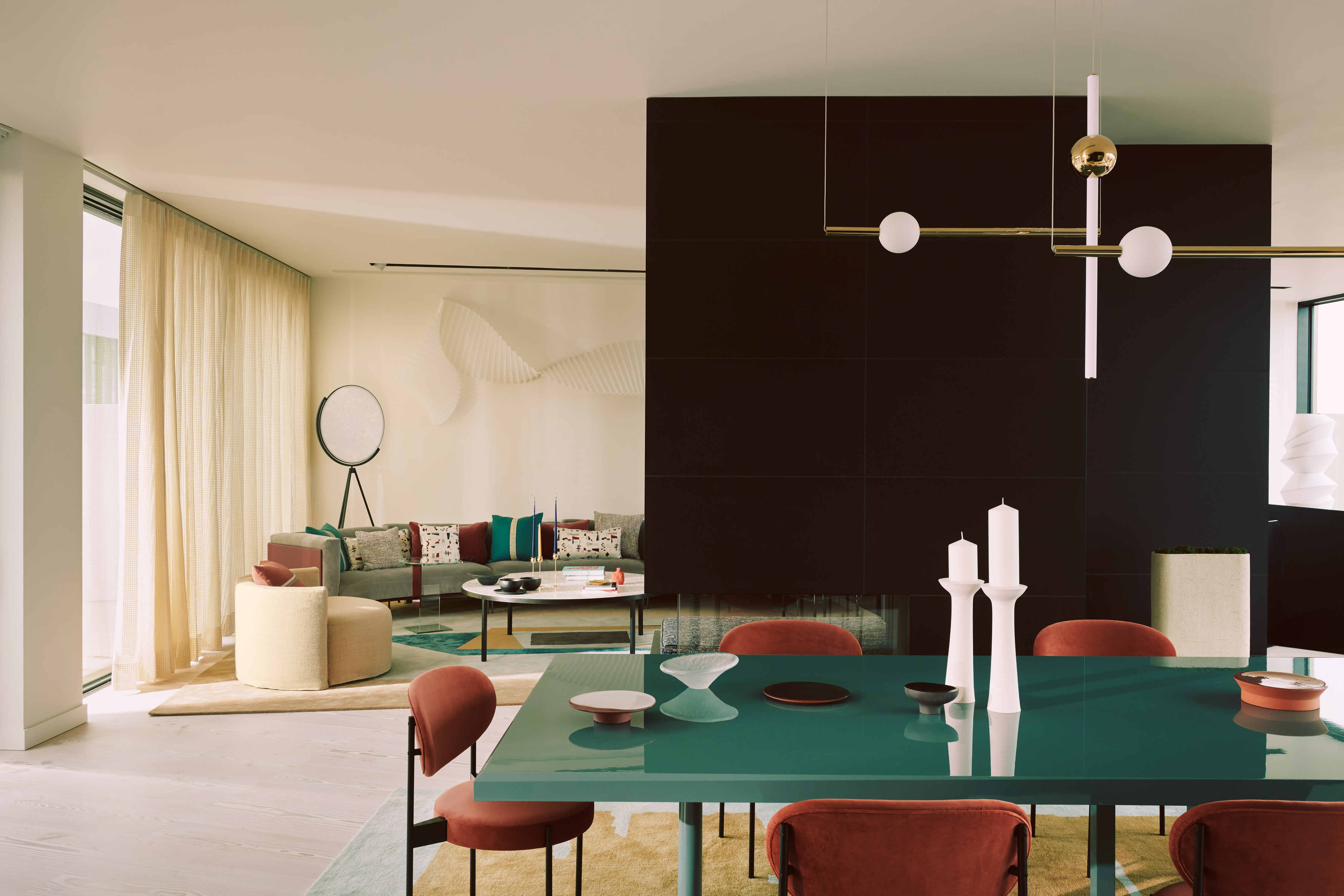 Apartment interior with colorful furniture like a teal dining table with rust colored chairs.