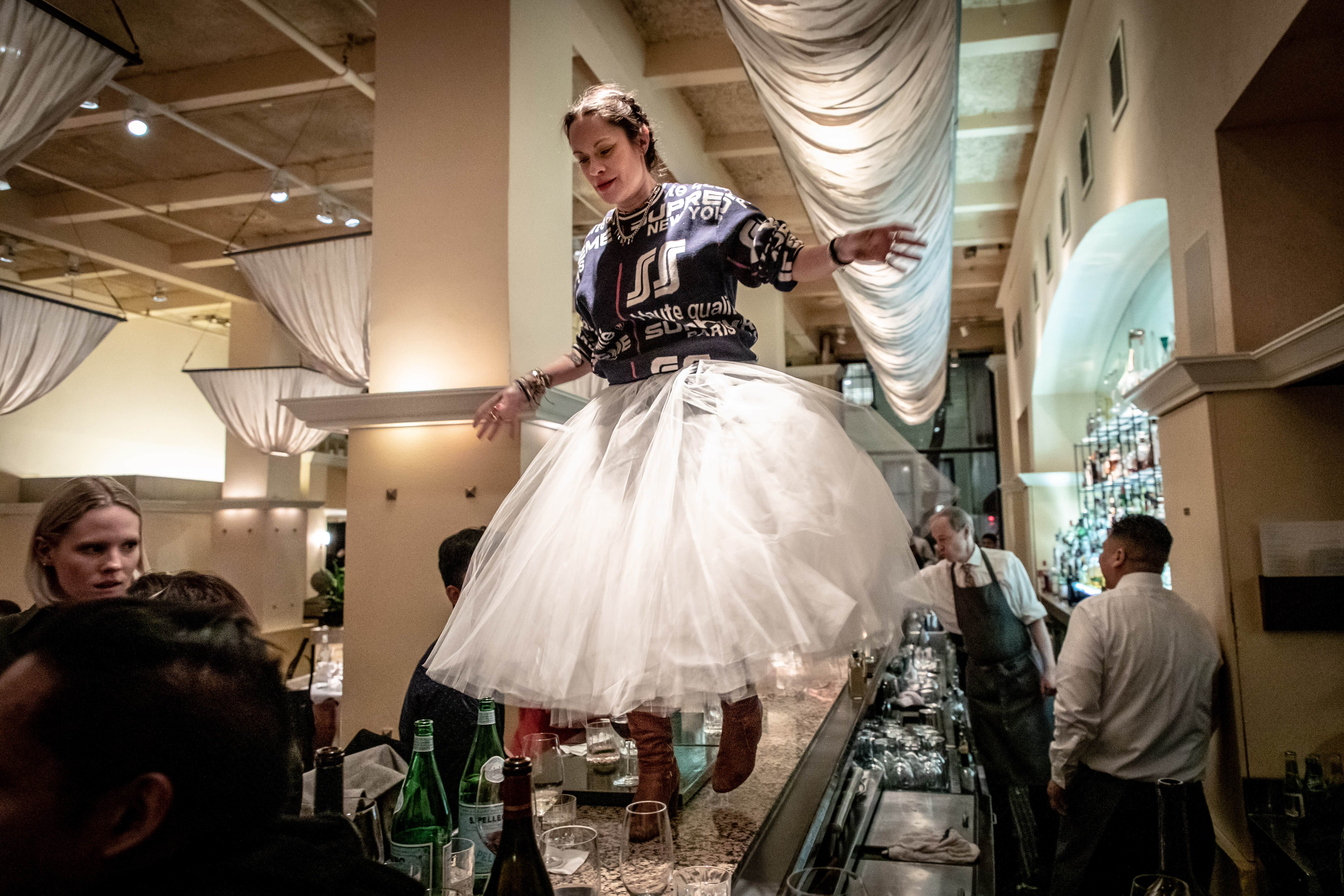 Regular customer Bianca Jebbia, wearing a giant white tutu, stands on top of the bar at Gotham