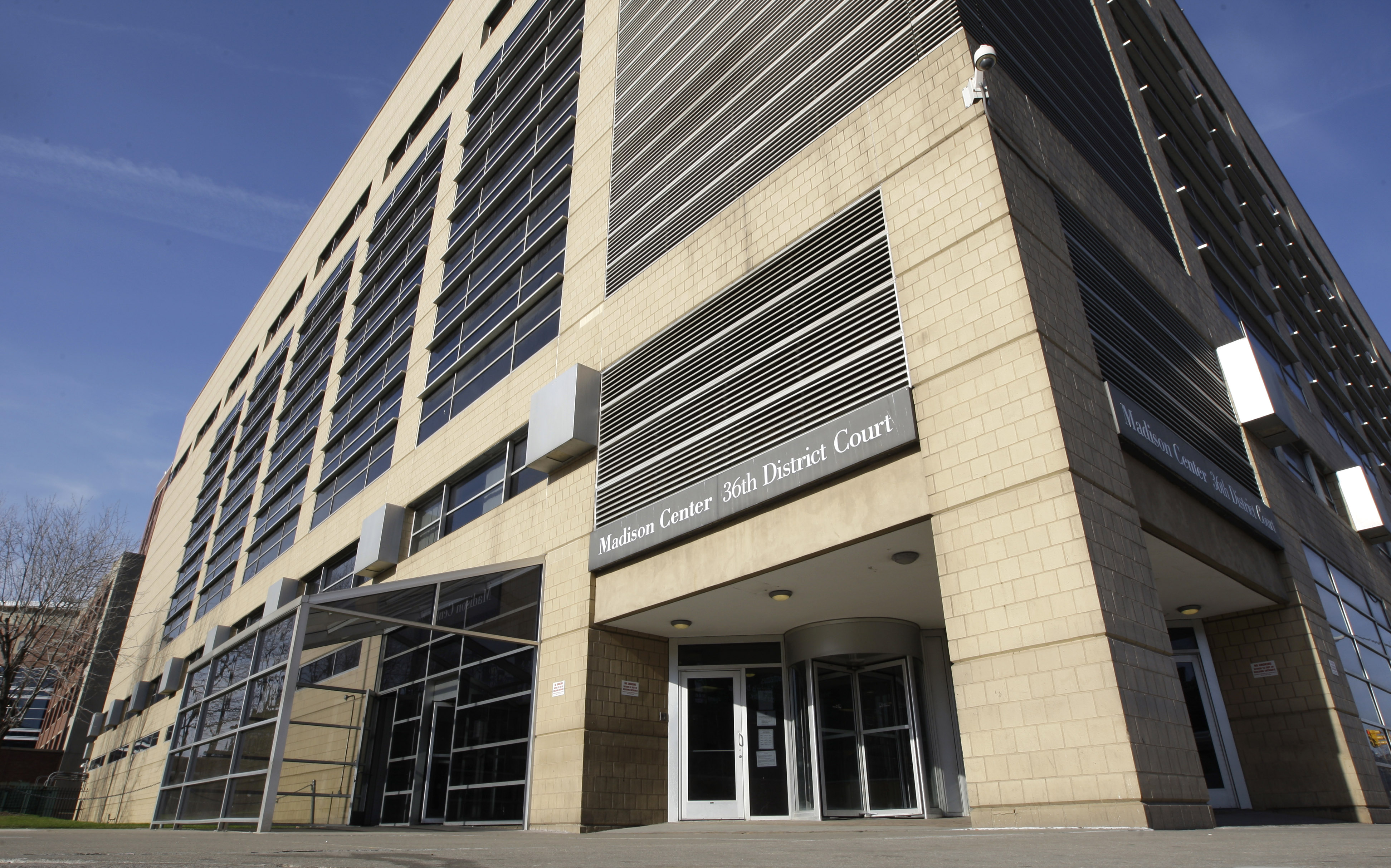 """A tall white brick and glass building. A narrow gray sign over a revolving door reads """"Madison Center 36th District Court."""""""