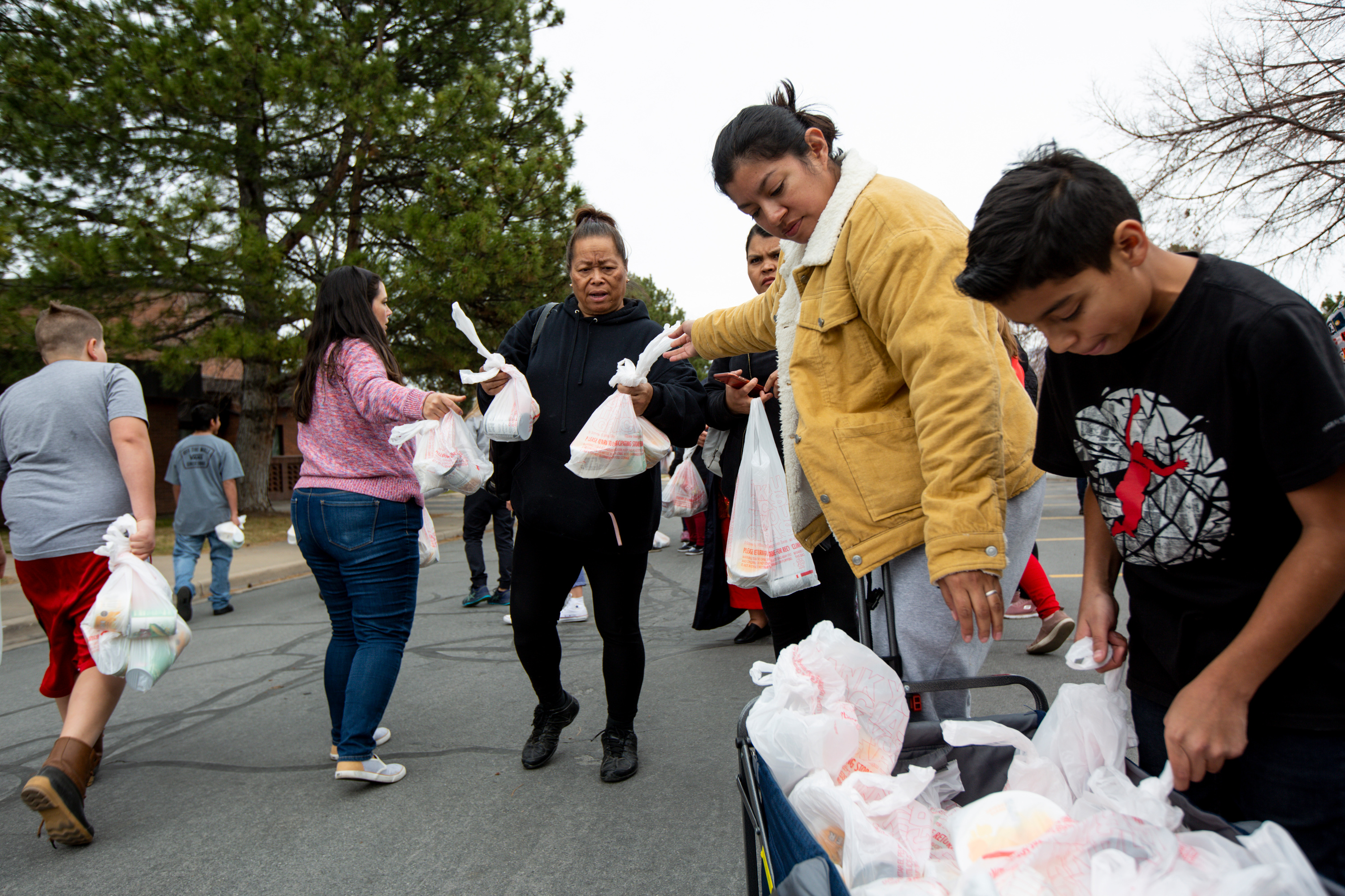 Mele Massey, center, collects the few donations left from the Utah Food Bank at the parking lot of a chapel belonging to The Church of Jesus Christ of Latter-day Saints in Taylorsville on Monday, March 16, 2020. Hundreds of people waited in line to receive the donations.