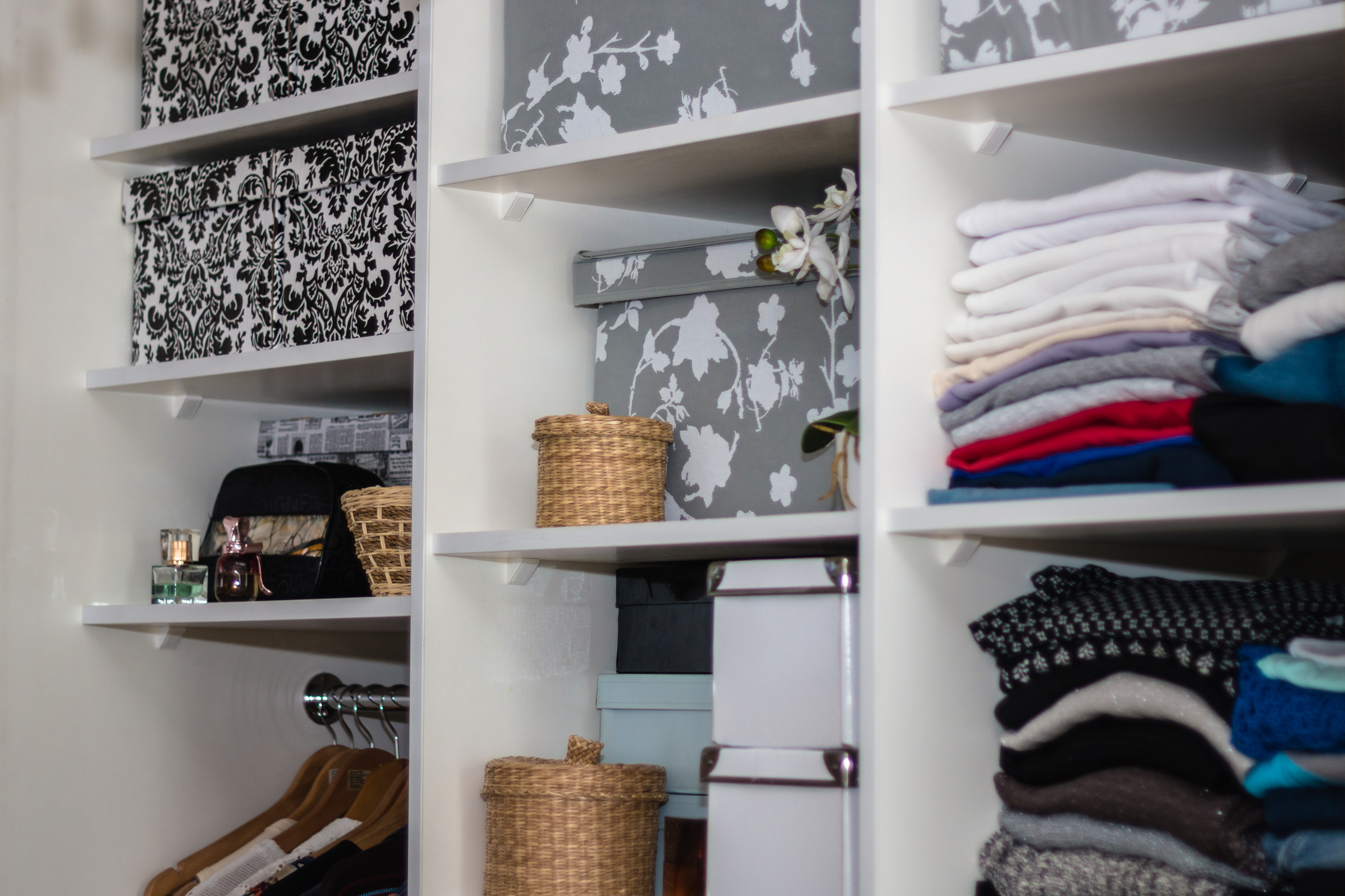 A smartly organized closet with shelves and a portion for hanging clothes.