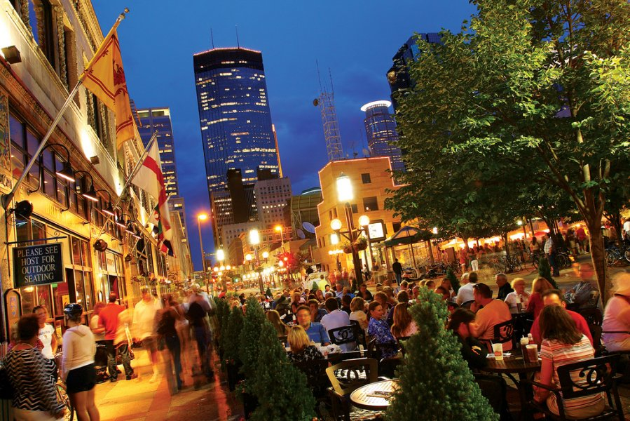 A summer nighttime view of downtown Minneapolis overlooking a full patio with the IDS tower in the background