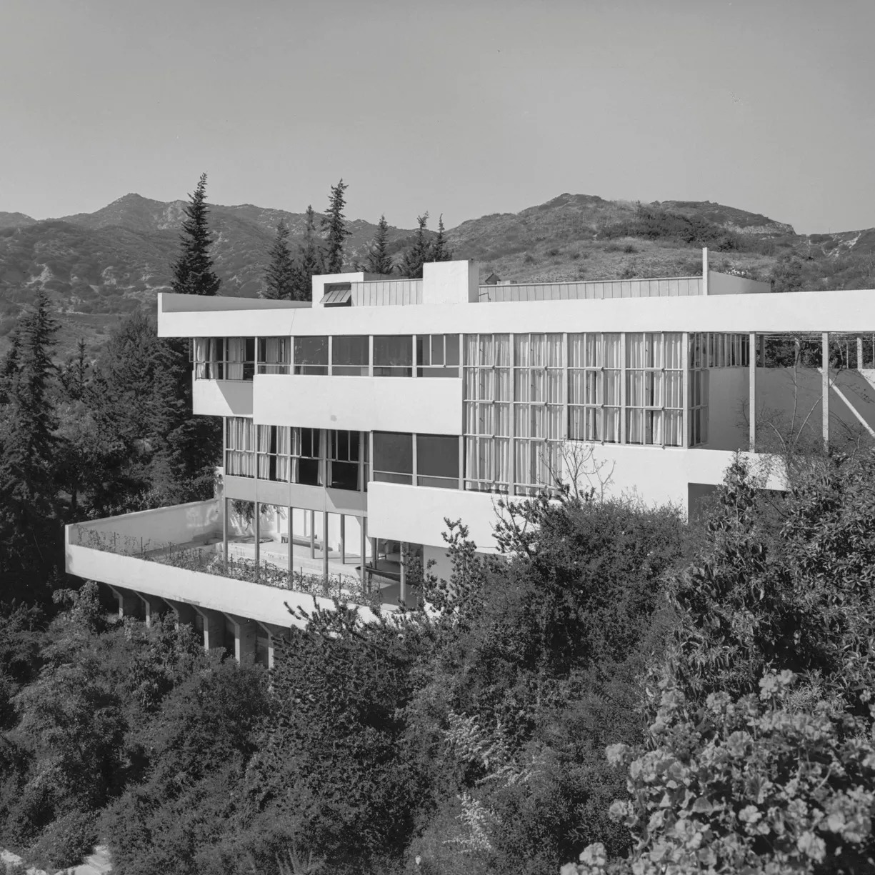 A black-and-white photo of a multi-story modernist house with large windows, porches, and a roof deck.