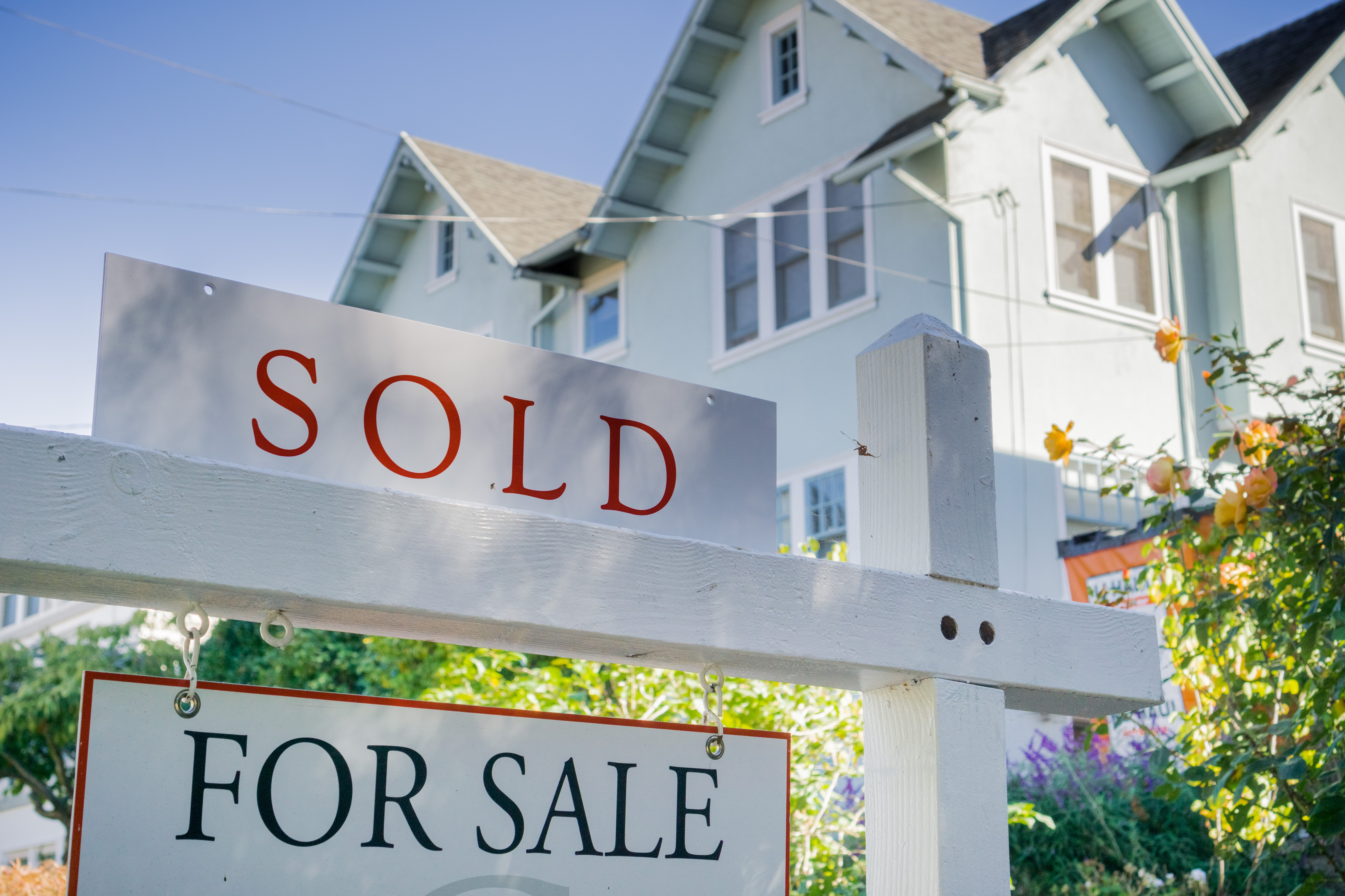 """A for sale sign with the word """"sold"""" above it and a house in the background."""
