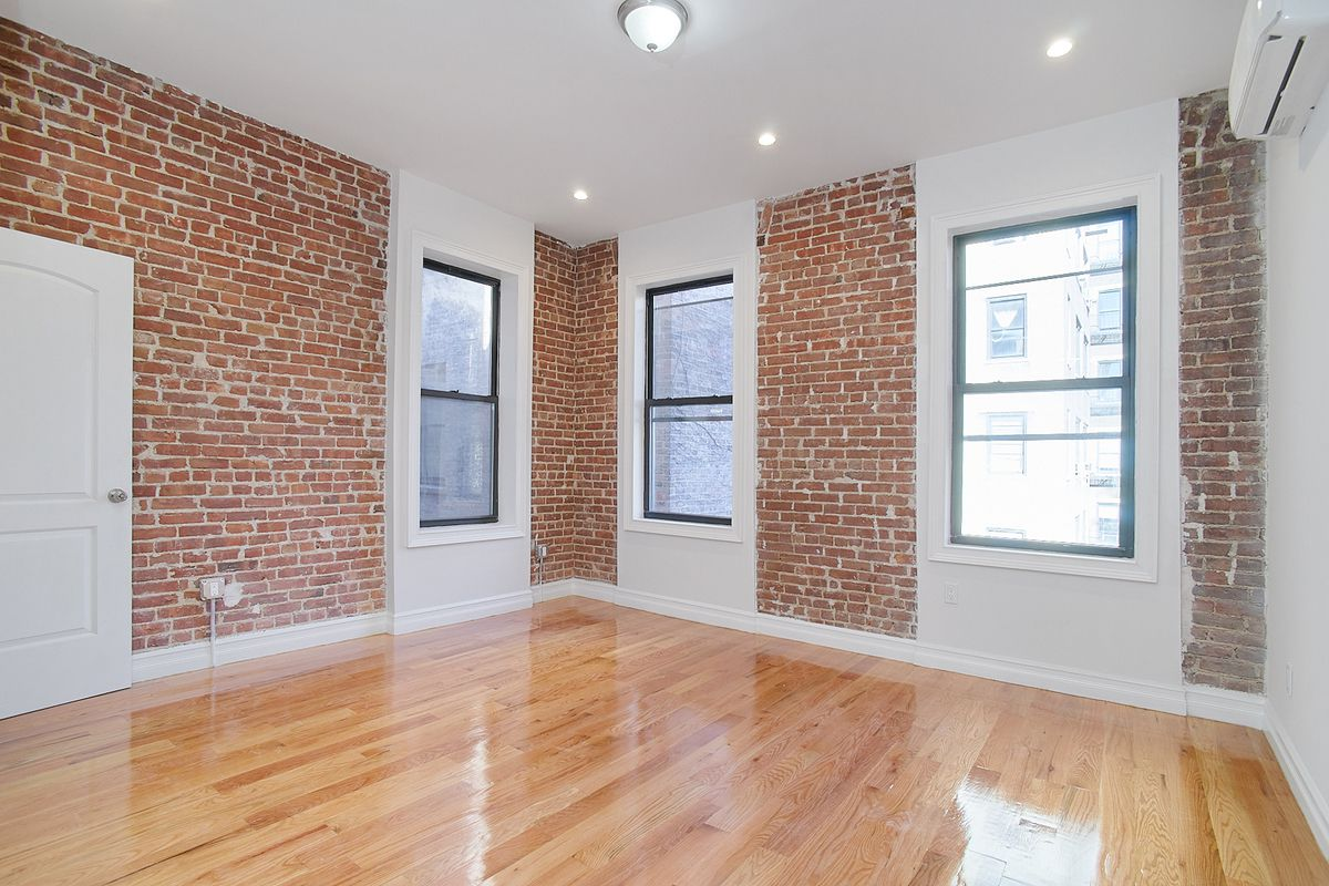 A living area with exposed brick and three windows.