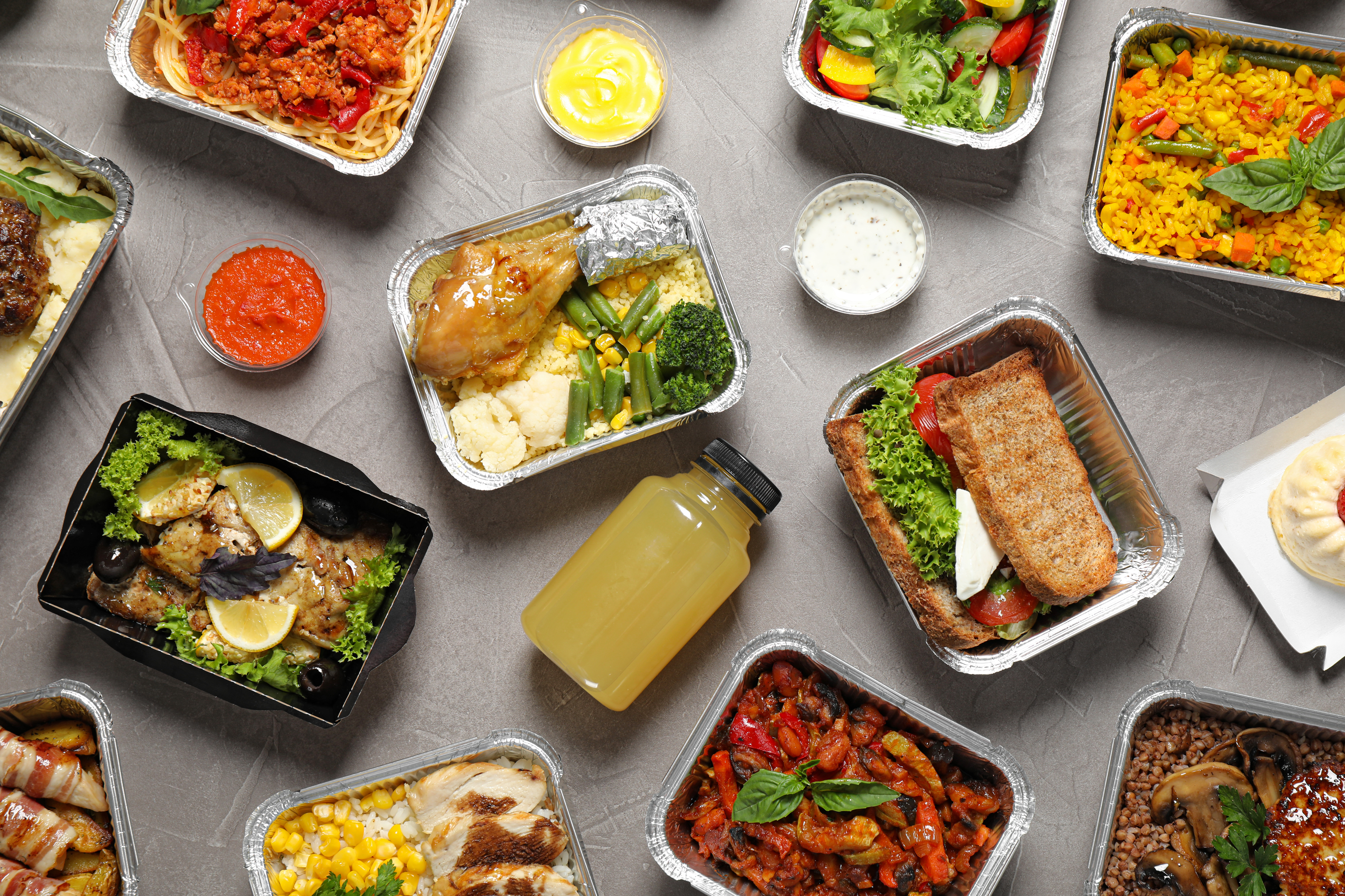 A selection of different kinds of food in a variety of takeout containers, with sides of sauce.