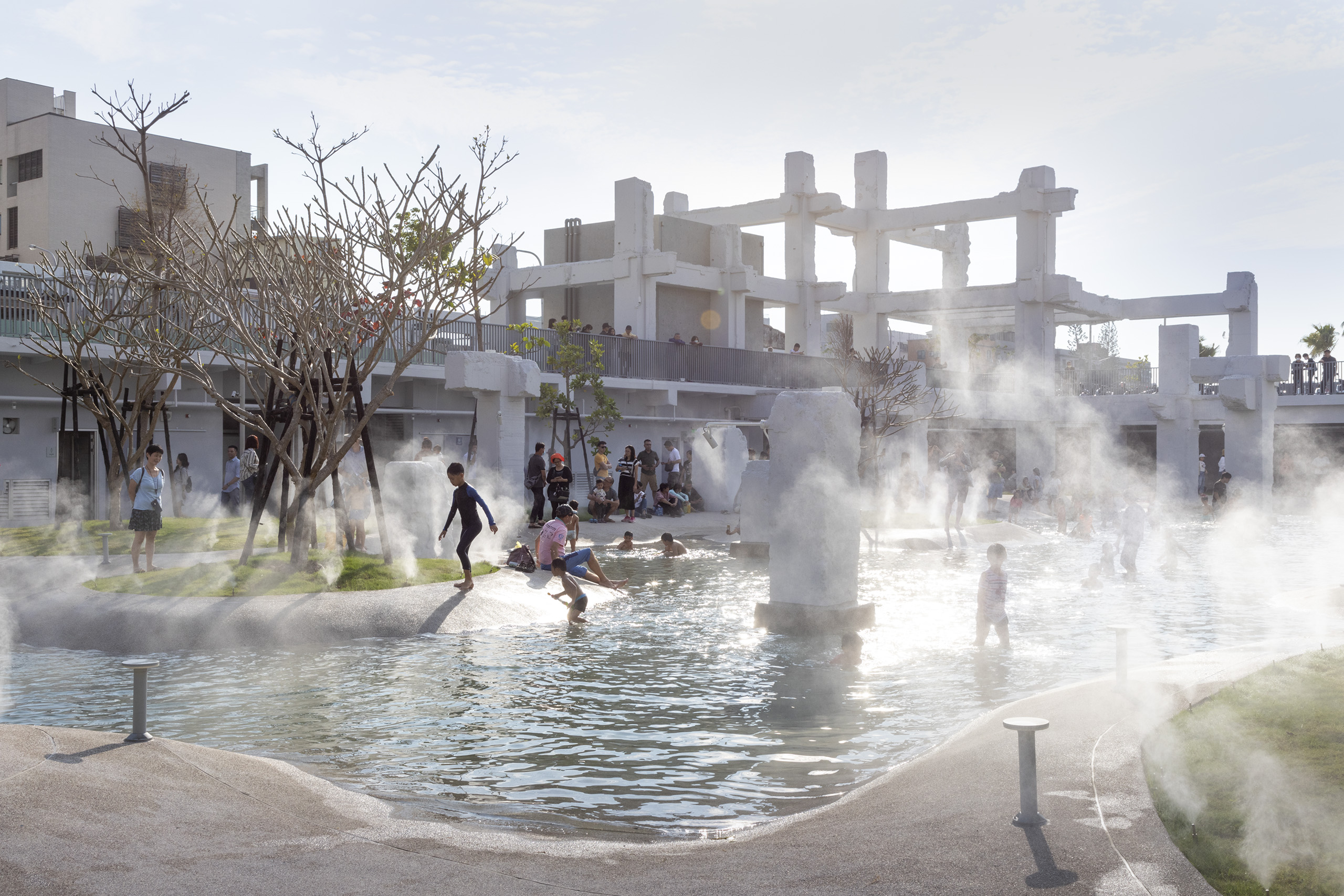Children playing in wading pool with beamed structures in the distance.