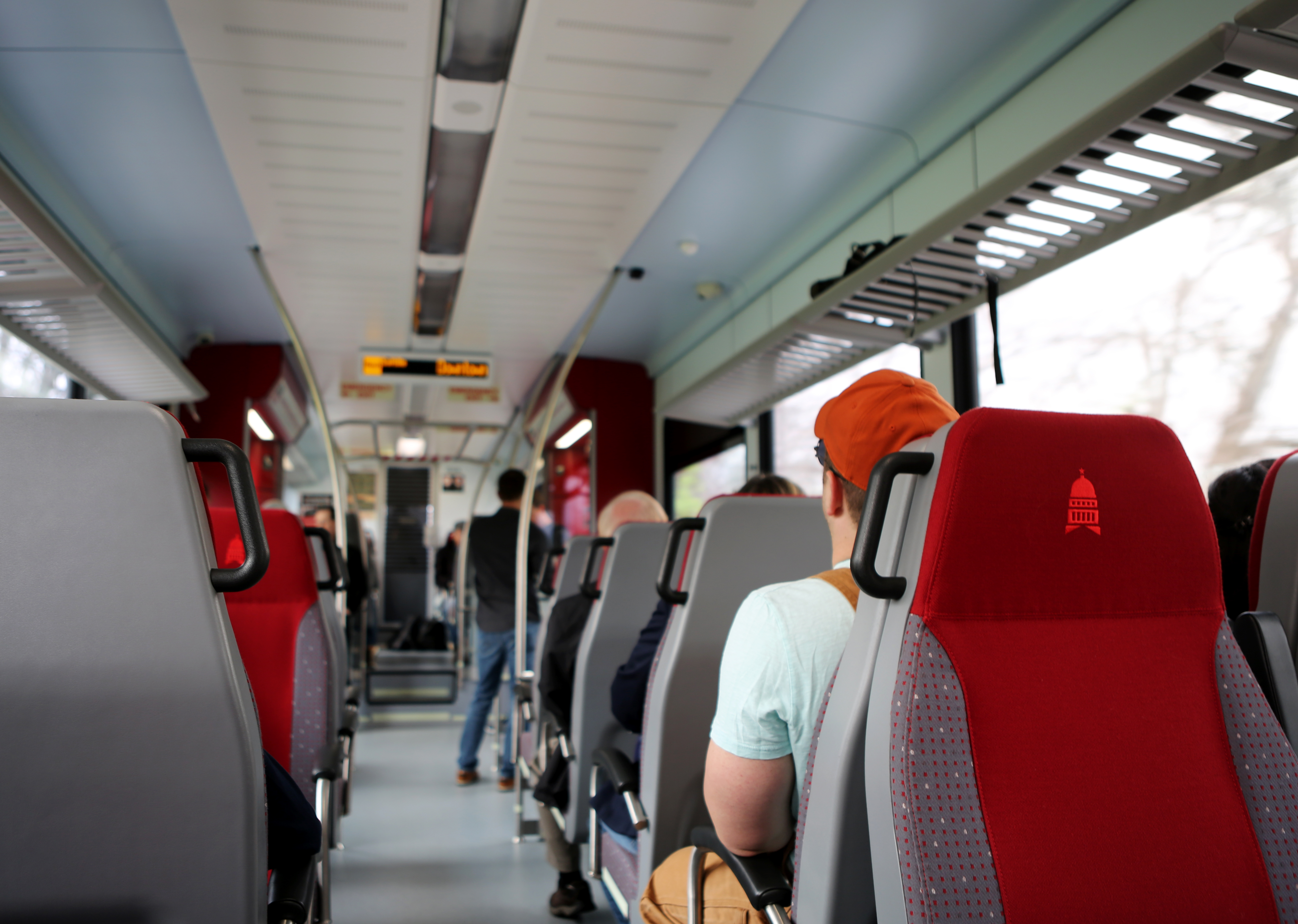 Interior of a bus with aisle in center and chair backs to the camera. There are people in some seats and a person standing and holding a pole in the front.