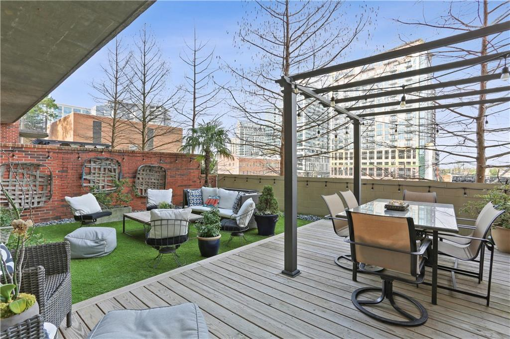 A large deck and patio at a condo with sky rises beyond.