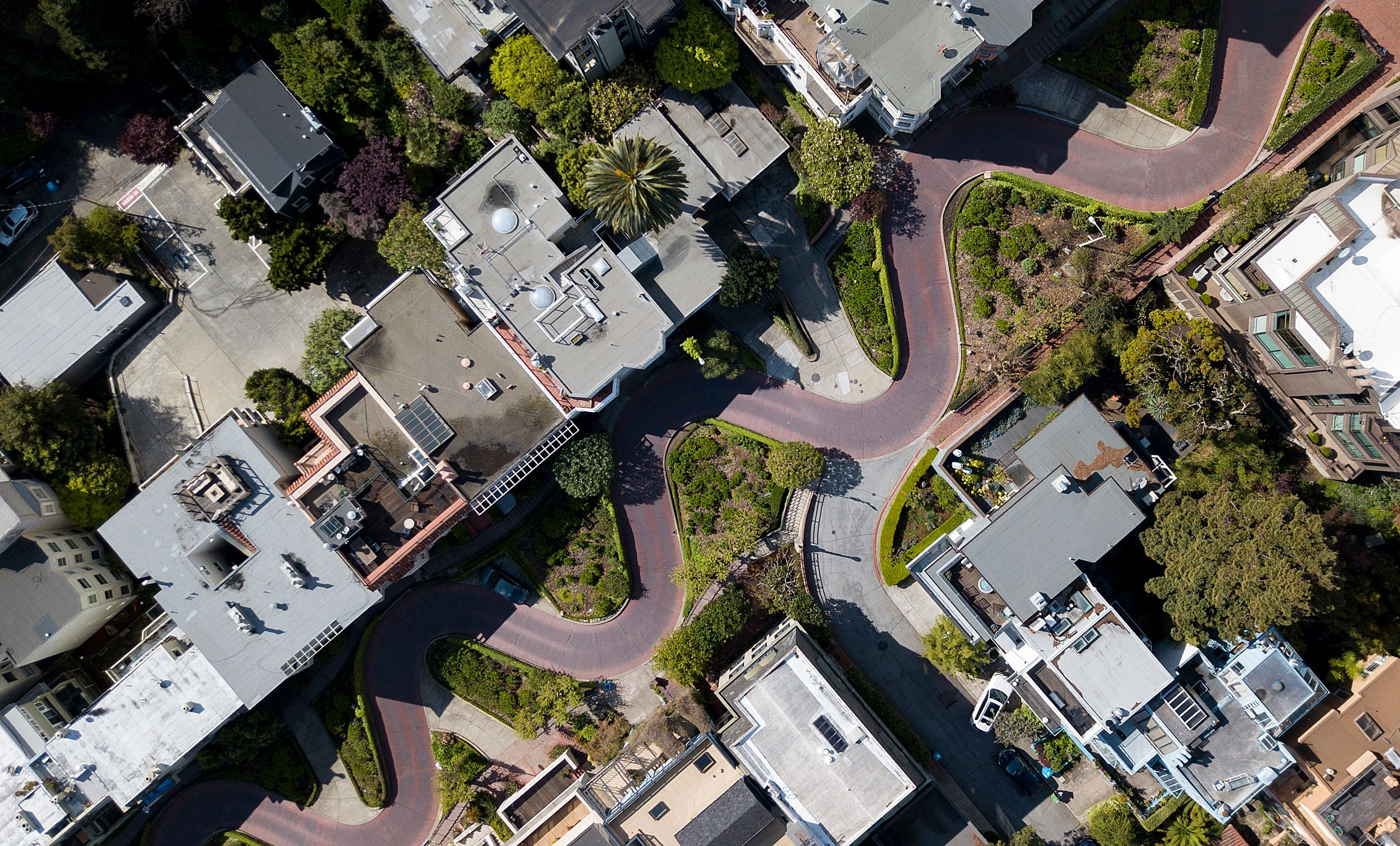 An aerial view of a curvy street with no cars on it.