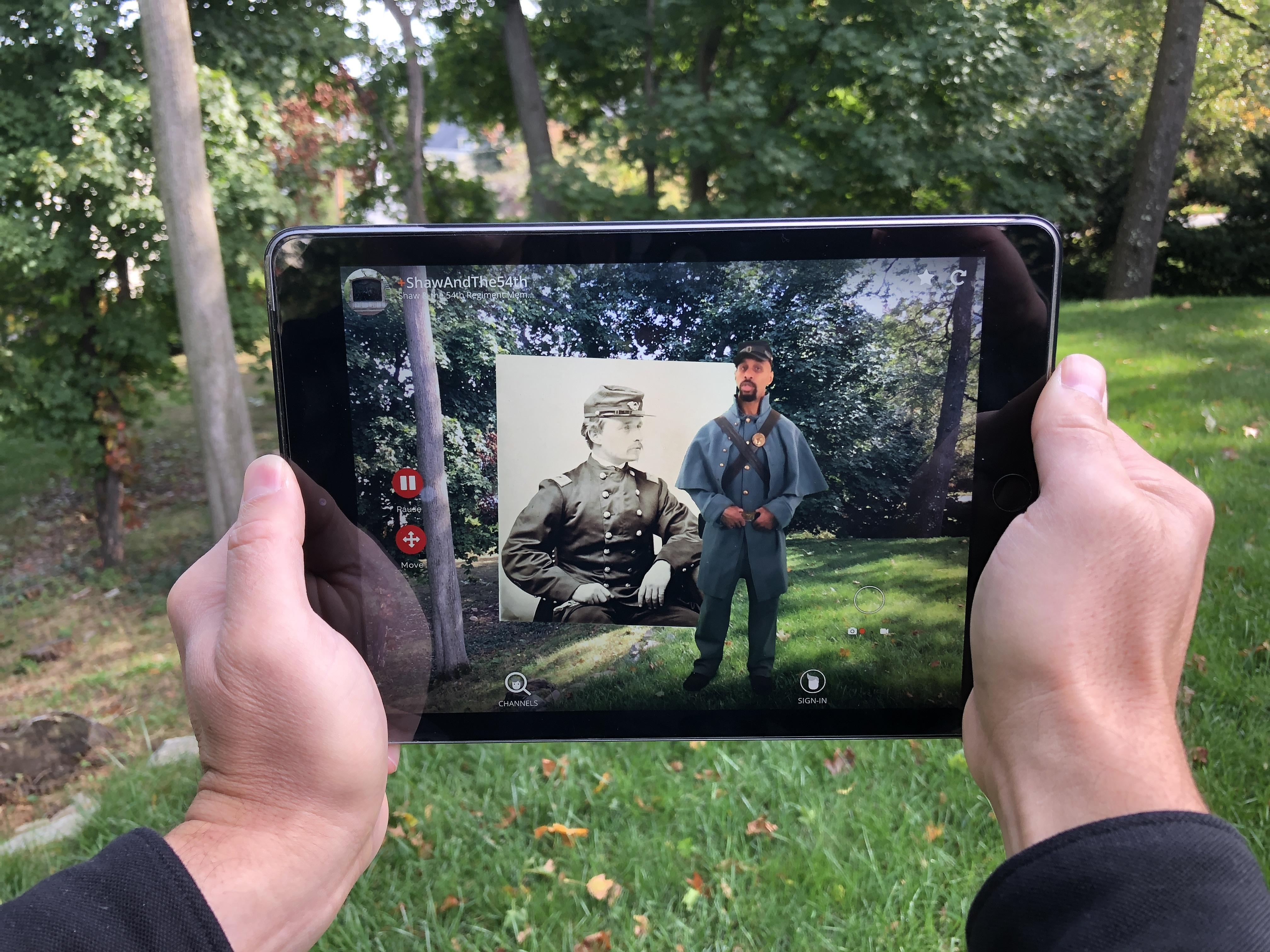 Two hands holding a digital tablet with an actor in Civil War soldier garb giving a lecture.