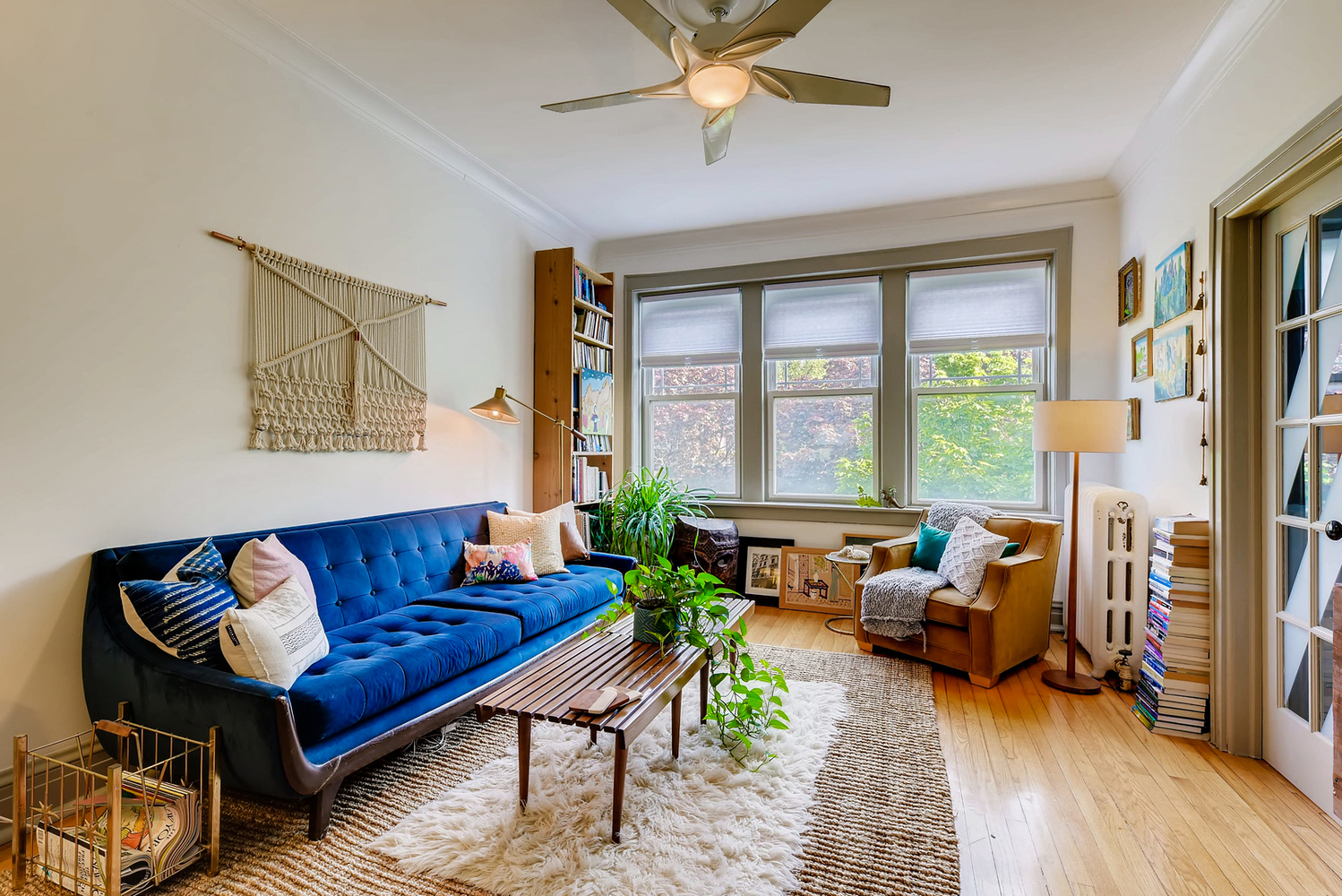 A photo of a living room with a blue couch, a large three-panel window, and a coffee table with a shag rug.