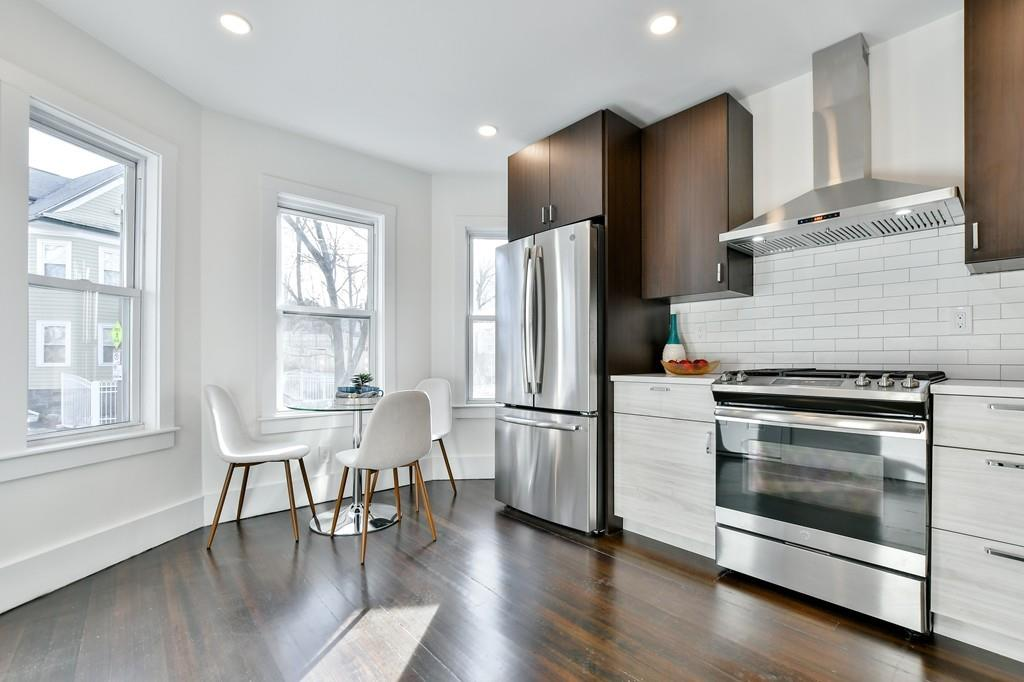 A modern, open kitchen with a counter and a small table with chairs.