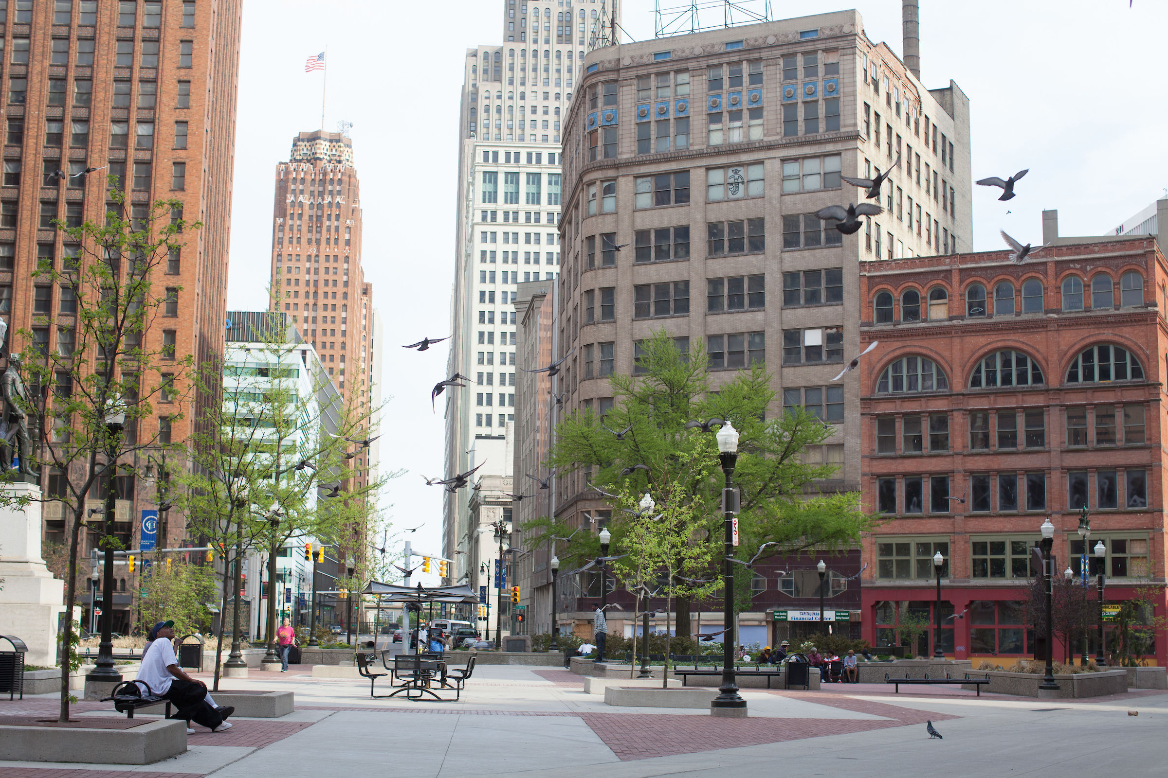 A plaza surrounded by tall buildings. There's a man sitting on a concrete planter around a tree.