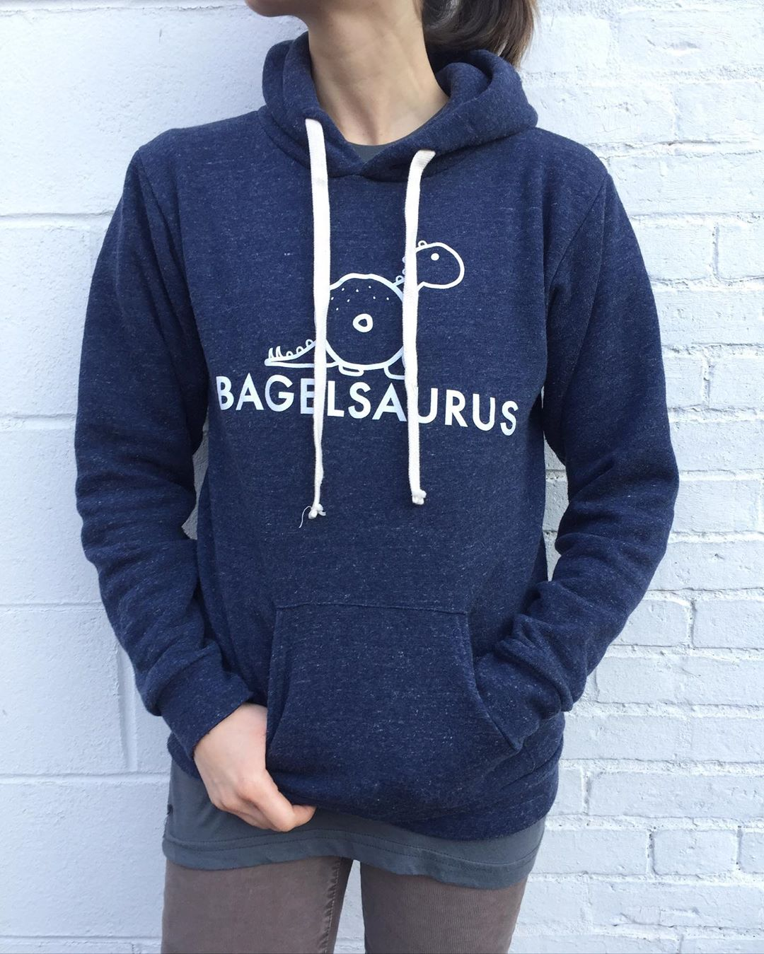 """A person (face is cut off at the top of the photo) models a navy blue hoodie with the word """"bagelsaurus"""" and an image of a dinosaur with a bagel for a body"""