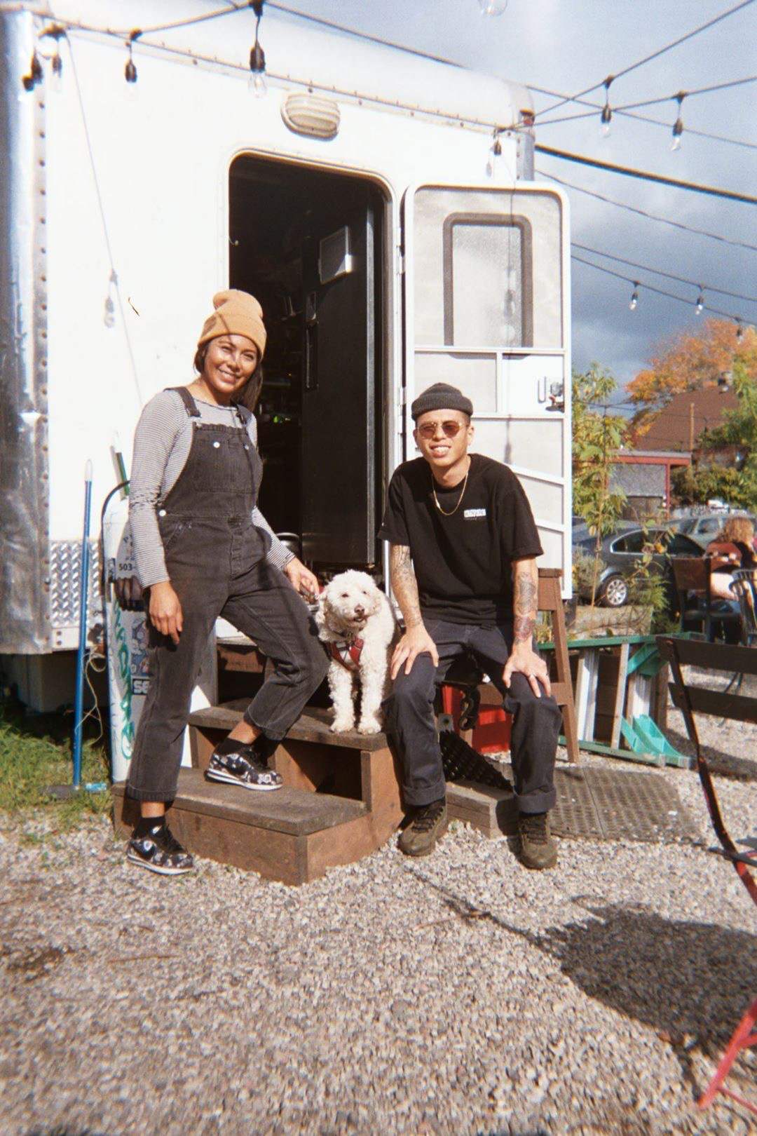 A woman in a beanie and overalls stands outside a food cart, holding a white dog on a leash. A man sits on a stool outside the cart, wearing sunglasses and a beanie.