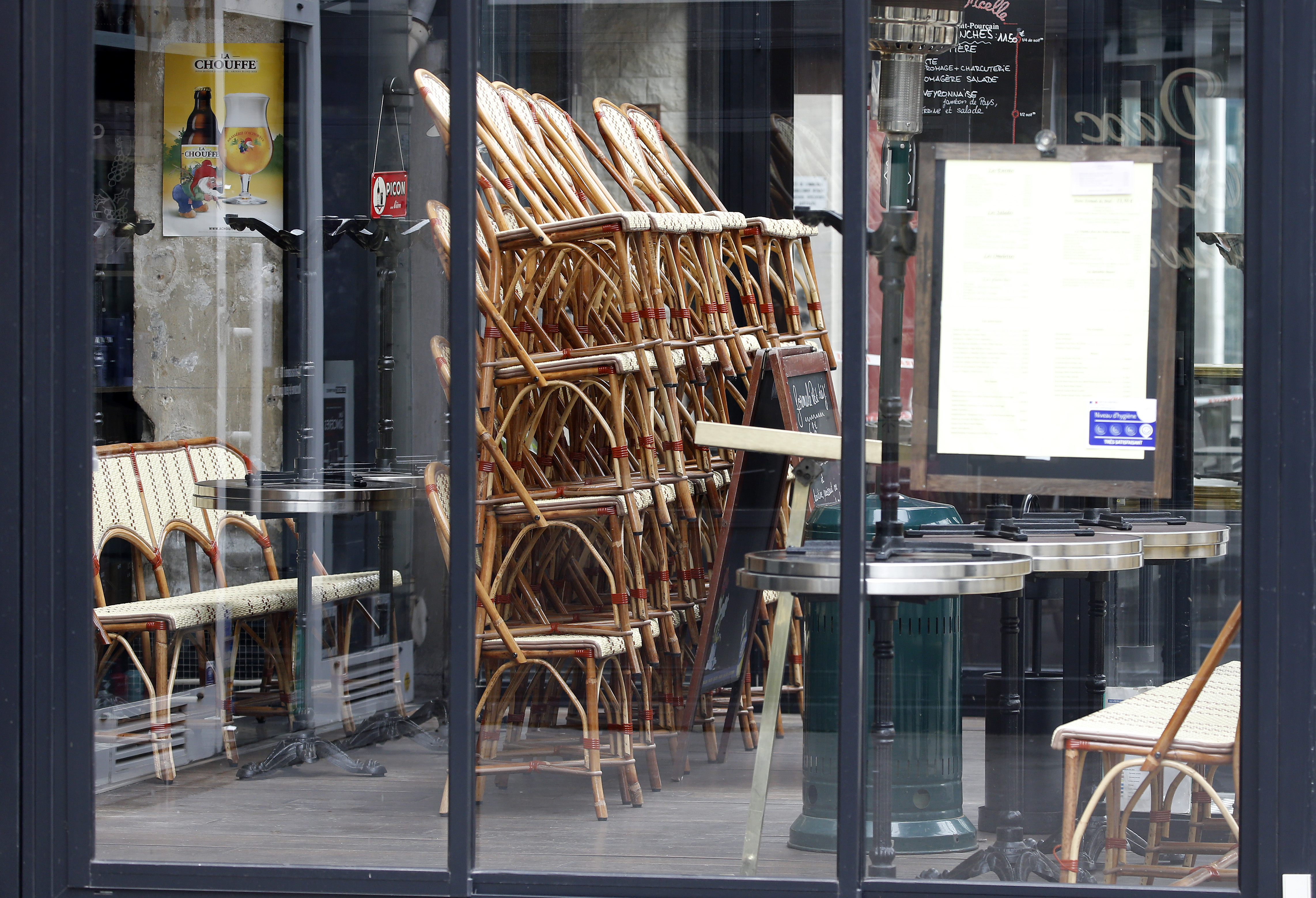 Stacked chairs inside a restaurant seen through the restaurant's window