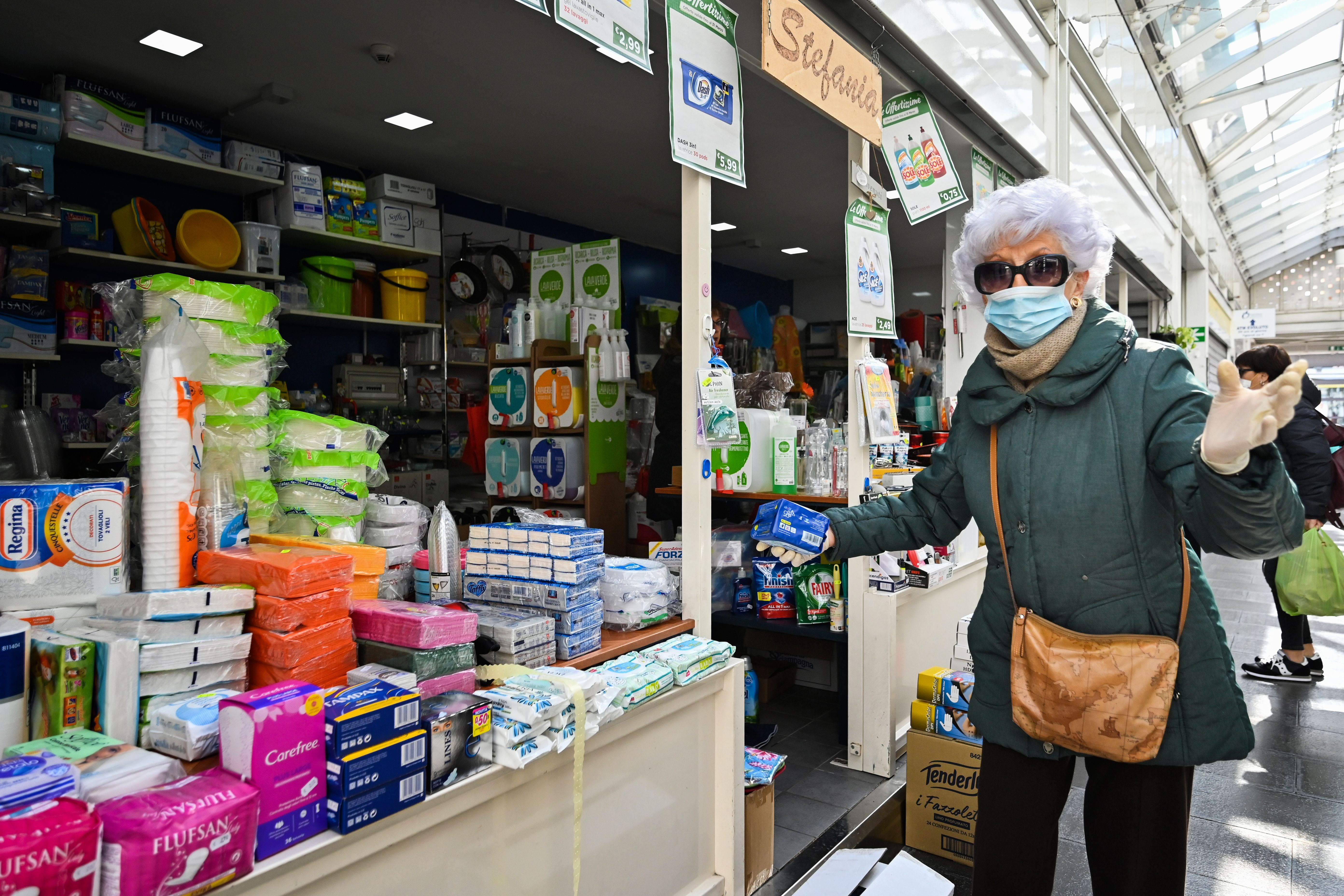 A senior citizen shops while wearing a surgical mask and rubber gloves.