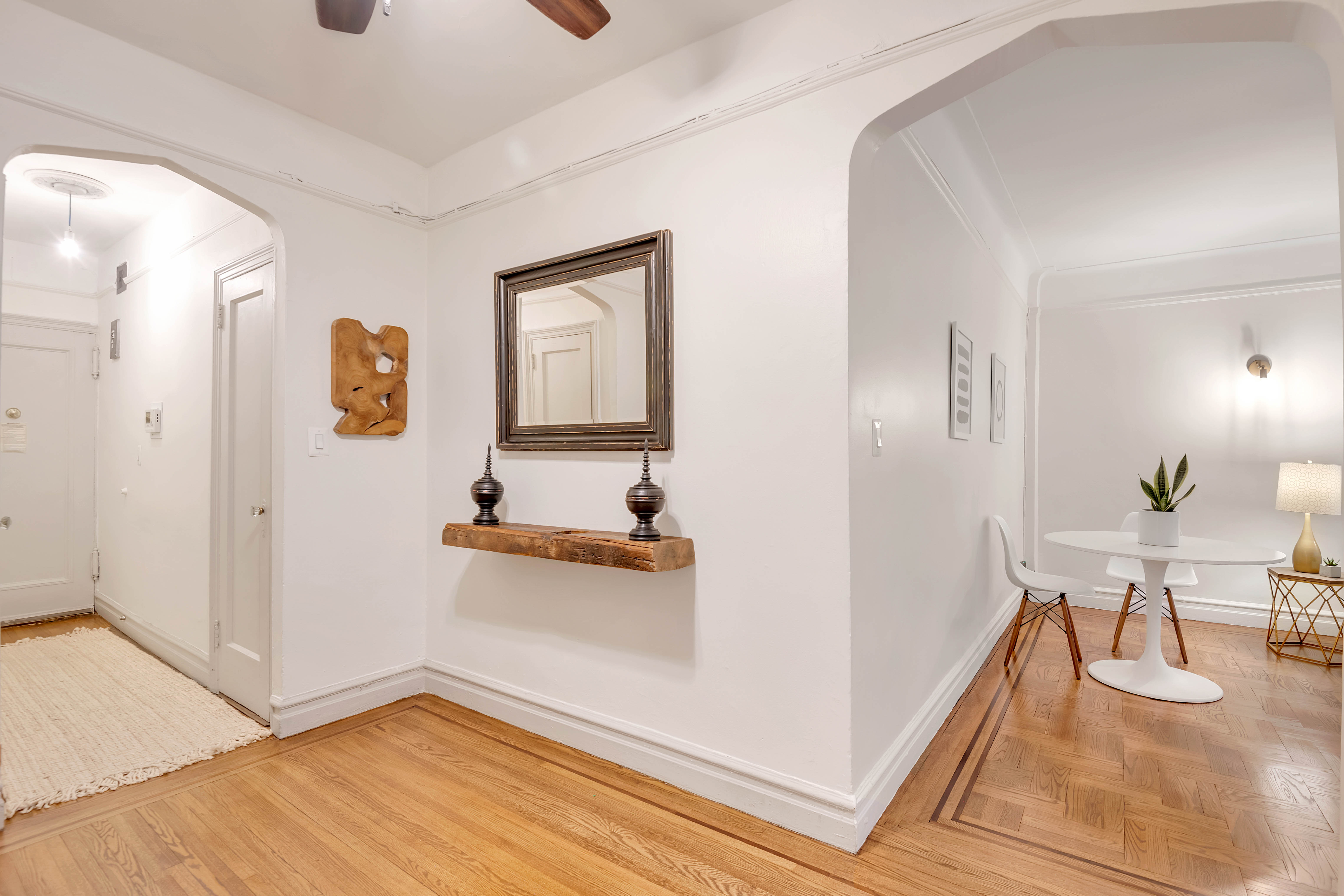A foyer with arched entryways, hardwood floors, a mirror, and a ceiling fan.