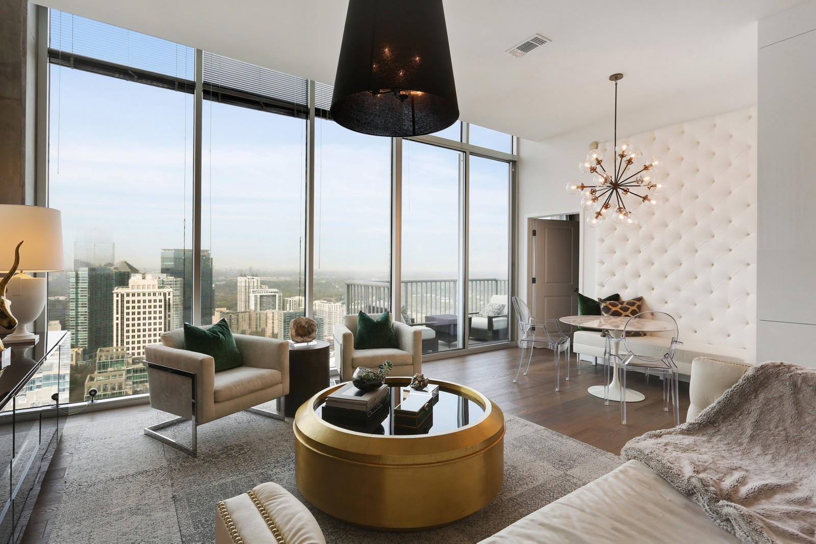 A huge living room of a condo with white walls overlooking a large city.