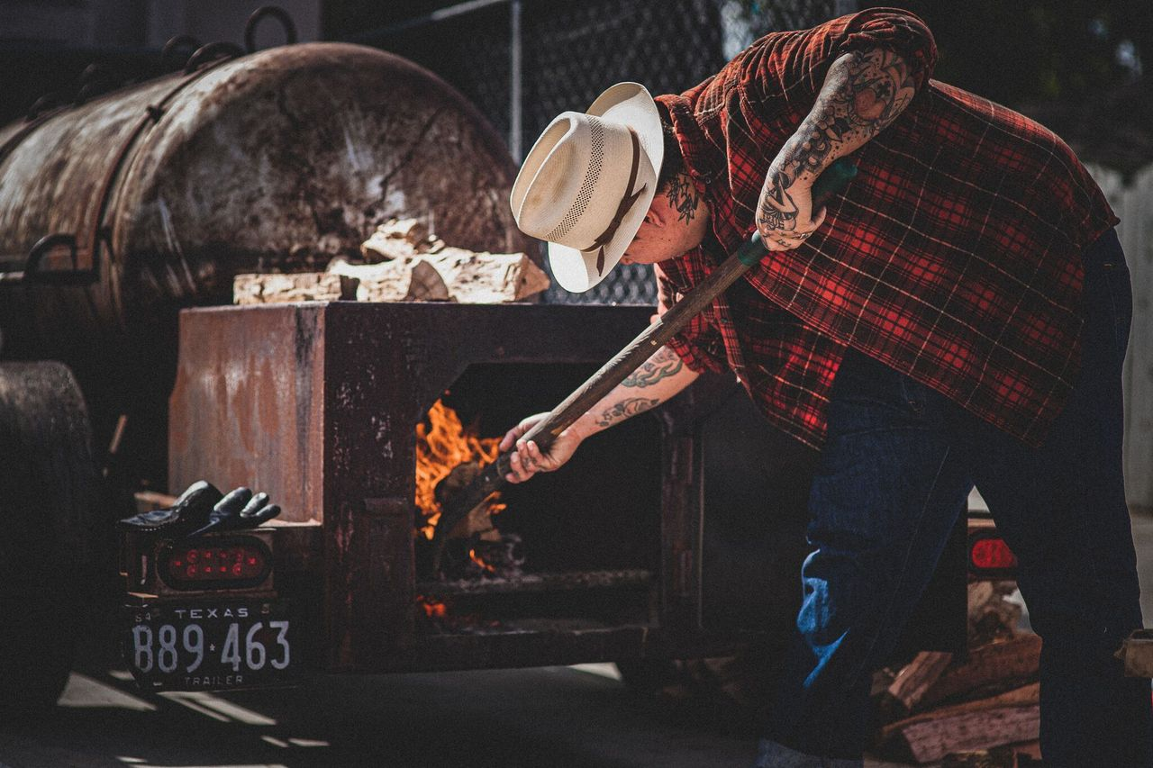 A man in a white hat and red checkered shirt tends to a fire inside of a barbecue pit.