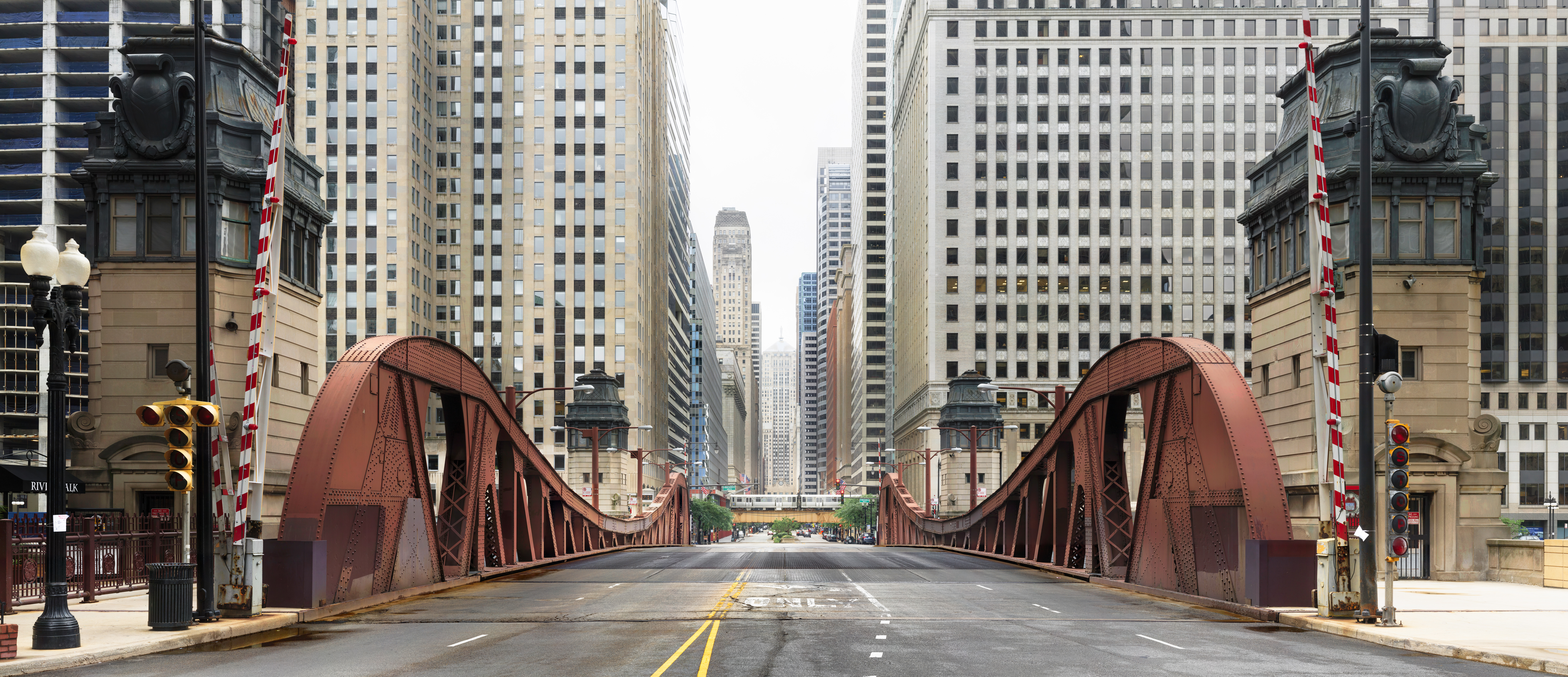 A view down a metal bridge leading to a dense urban street with glass and stone skyscrapers on either side.