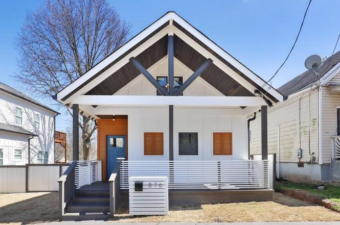 White house with A-frame roof lines, wood shutters, gray/blue door, and covered front porch.