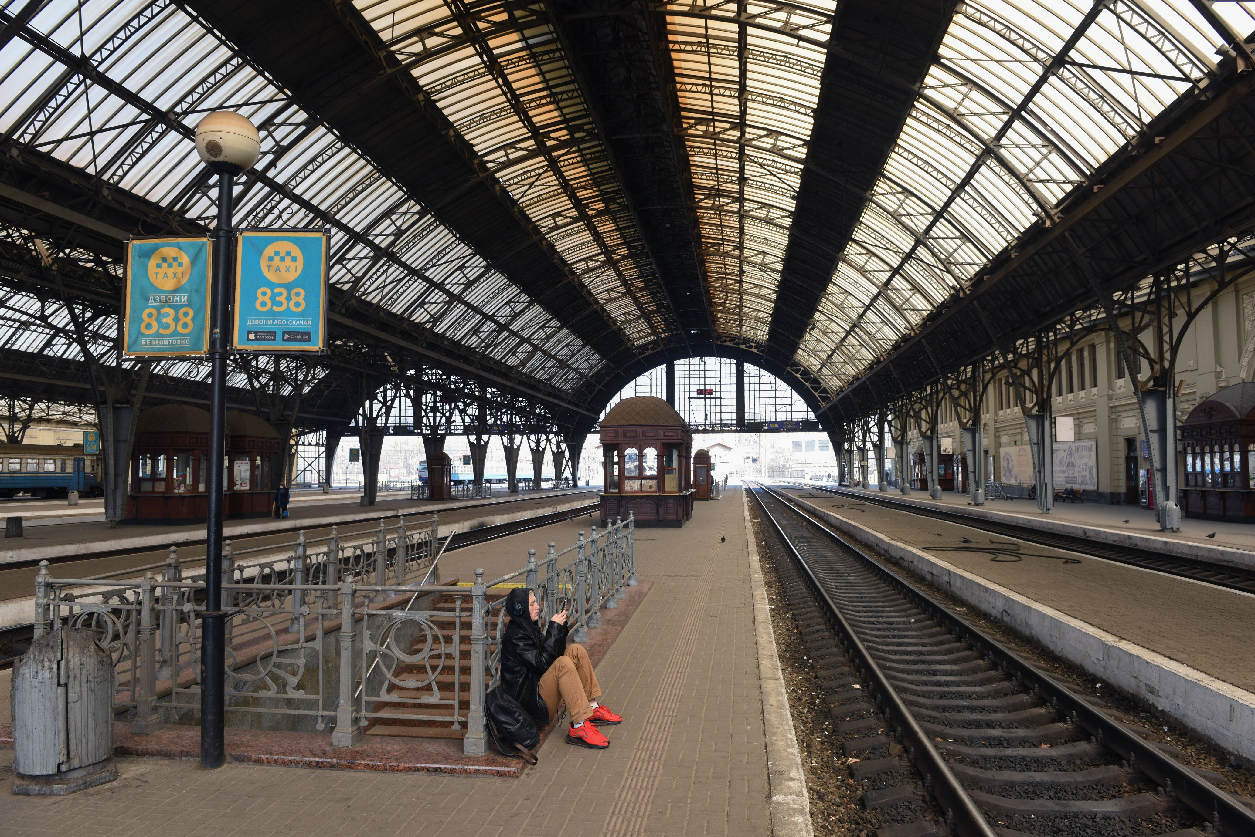A man in an empty train station looks at his phone.