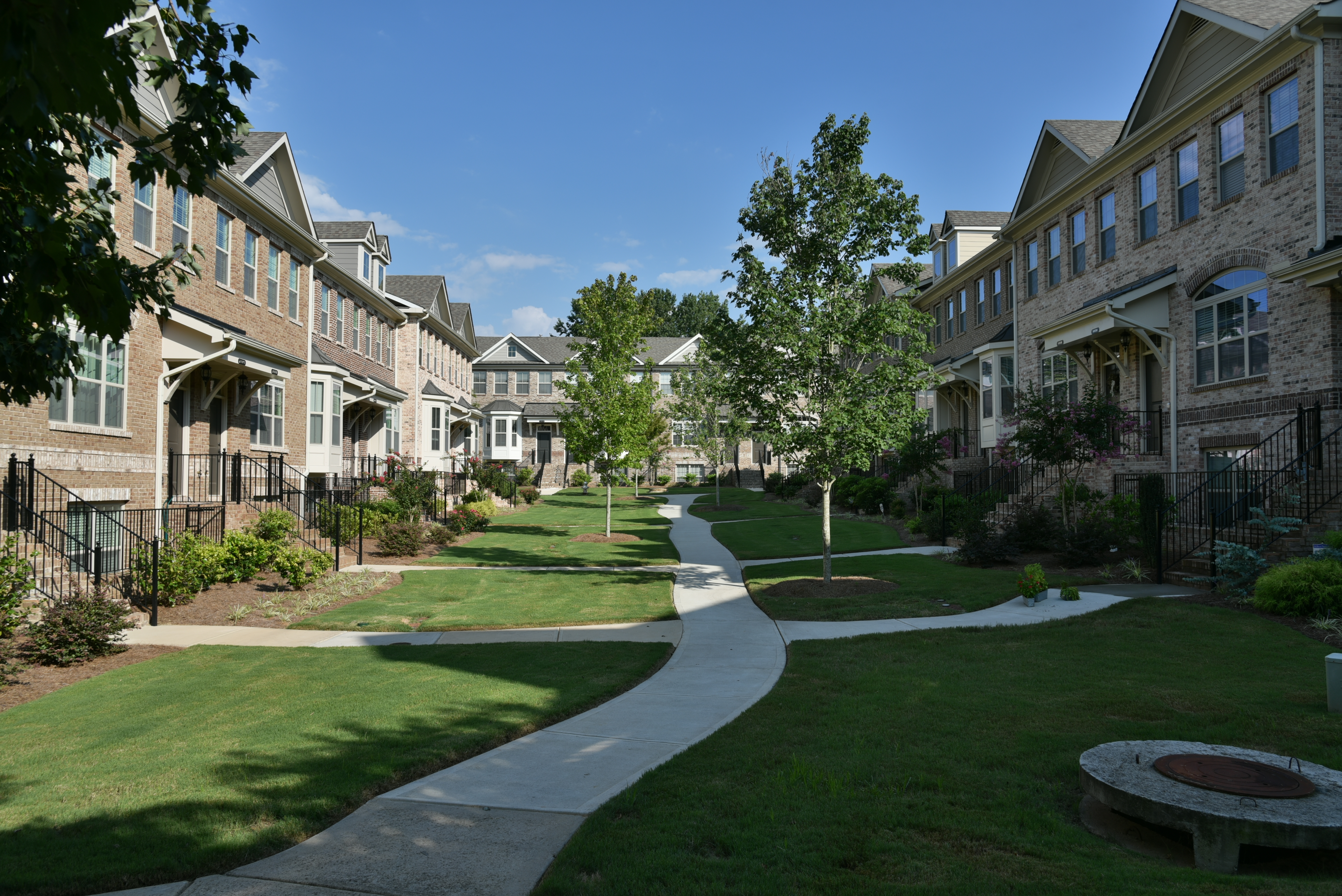 Two rows of townhomes on either side of a green space with a sidewalk in the middle.