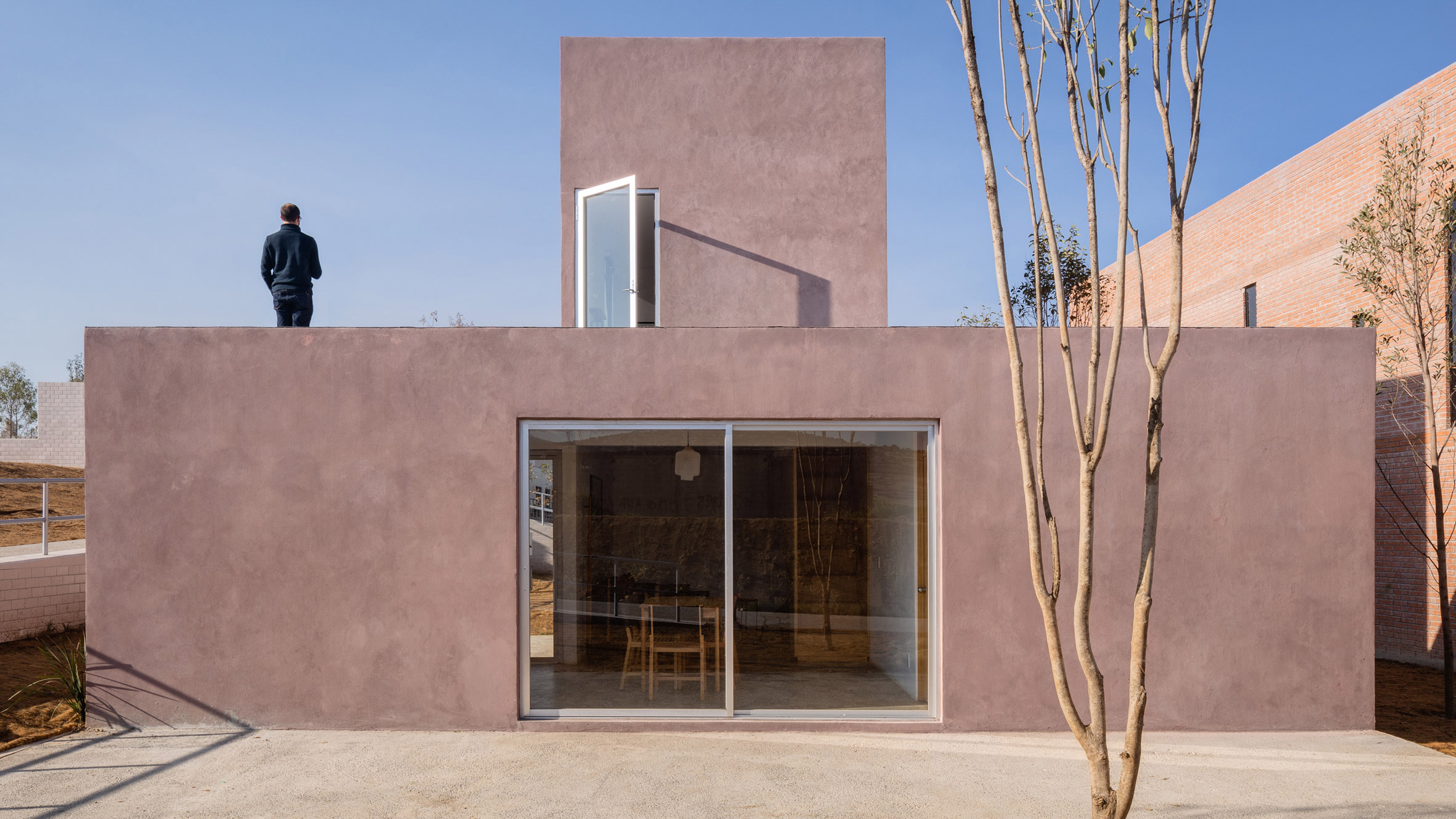 Man standing atop pink concrete house