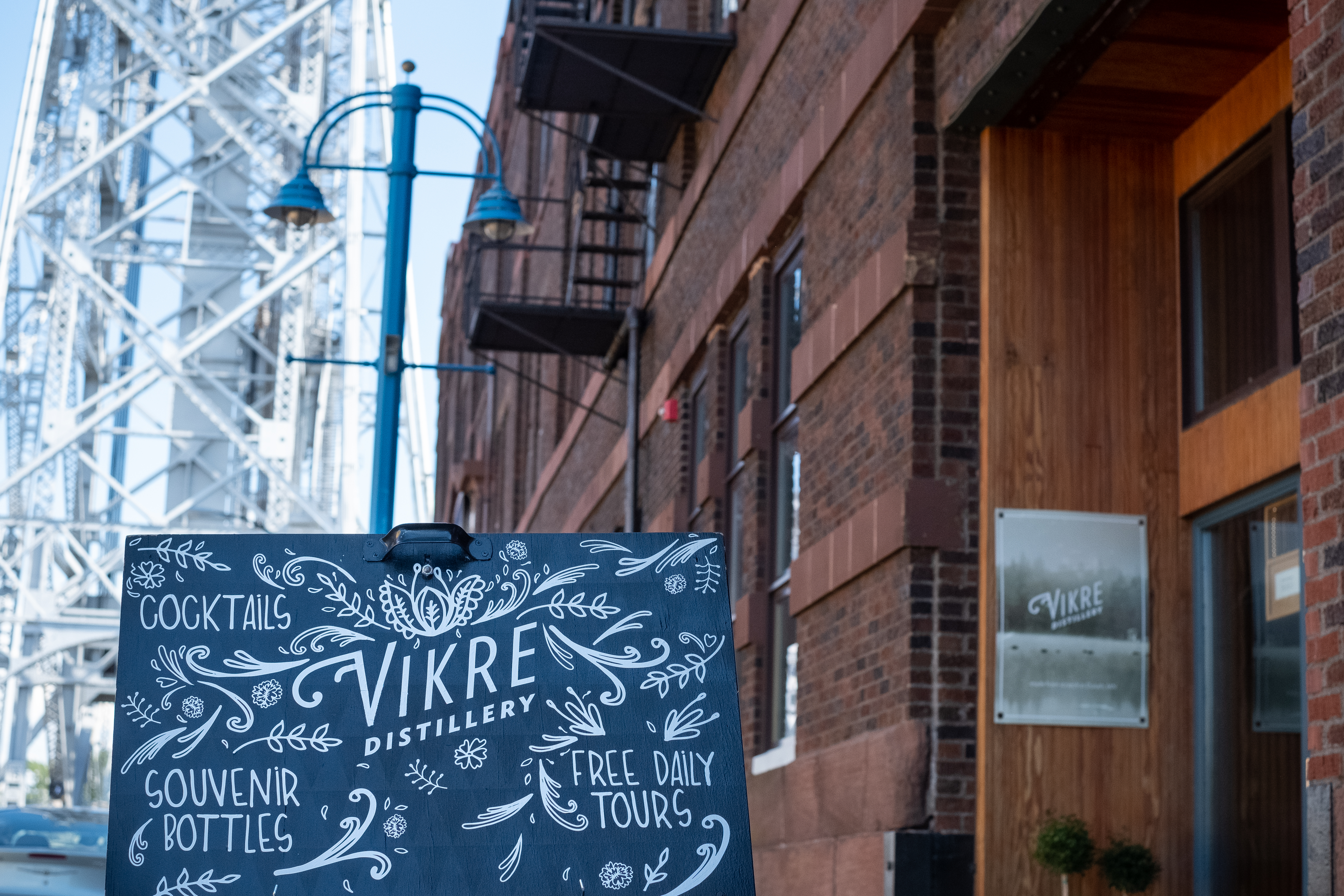 A chalkboard sign outside of the distillery in Duluth with the aerial lift bridge in the background
