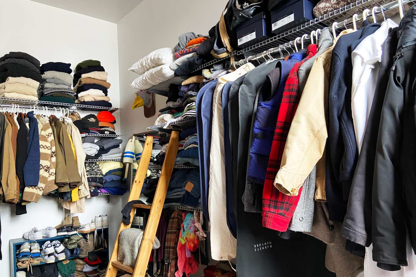 Closet lined with a wall of clothes.