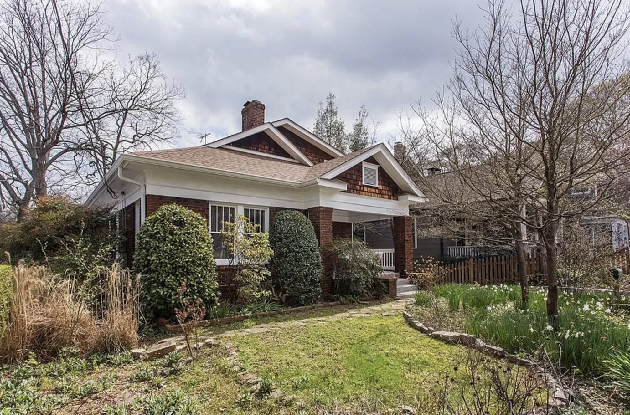 Brick house with white trim sits behind a front yard landscaped with trees, shrubs and flowers.